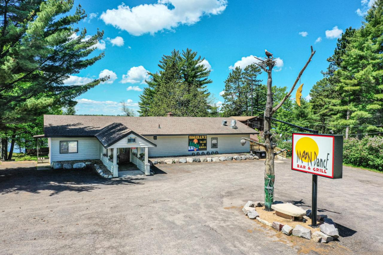"""Moondance is a well-established bar and grill located on Hwy 17 between Rhinelander and Eagle River in the heart of Sugar Camp with 92 feet of frontage on Mill Lake. This establishment has direct access to miles of snowmobile trails with public access to Sugar Camp Lake across the road. The bar is accented with vintage/antique décor in keeping with a """"Northwoods"""" flare. Moondance seats 60 people, not including the bar and 2 outdoor deck areas facing the lake. The kitchen is clean and well maintained with commercial equipment including dishwasher, walk-in cooler, range, hood, grill, and stainless-steel prep counters. The main level approximates 2600 square feet and includes a dining room, bar, and 2 public restrooms. Main floor also includes 2 offices and full bath which could be used as living quarters with a second living quarter and bath in lower level with walk-out to the lake. The owners have maintained this property over the past 21 years. Square footage to be verified by buyer."""