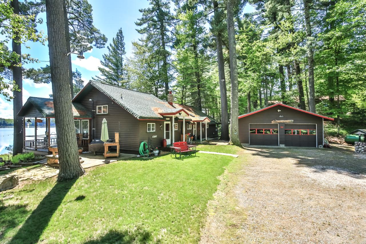 """Northwoods Charm to the """"T"""". This immaculately maintained year-round cabin sits just a stone throw away from the water. The original cabin was tied into a new addition in 2012. Wood throughout the home and great picture windows toward the lake create the perfect northwoods escape. The beach is complete sand and Fourth Lake is 253 acres in itself and part of the Moen Lake Chain. Plenty of space with 3 bedrooms, 2 Baths and 1,400 sq ft of main floor living. Private setting with a two car detached garage, water toy shed and professionally landscaped. A true hidden gem."""