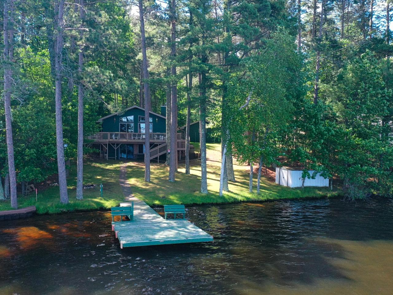 """The best location you can ask for on the Eagle River Chain of Lakes is on Wooded Lane. Situated on 1012 acre Catfish Lake, it is nestled in among some of the finest homes on the chain and it is in the middle of """"Boathouse Row"""". This 3+BR/2BA home offers 2201 sq ft of living space. The home features 2 stone FP's (gas) & an open concept living/dining/kitchen. It has an open & airy feel w/cathedral ceilings & wonderful lake views. The kitchen is fully equipped & has an island. The walkout lower level has 2BR's, & family room w/FP & a bar. When guests arrive, there is a """"honeymoon suite"""", an adorable 15' x 13' guest cottage w/bath. The lakeside deck is where you will want to relax in the summer. There are 2 garages so you can store most anything! One garage is over 1400 sq. ft. and the other is over 600 sq ft. The driveway is paved & the slope to the lake is gentle. There is a lakeside shed and the beach is perfect for swimming. The sunsets are an unforgettable experience there."""