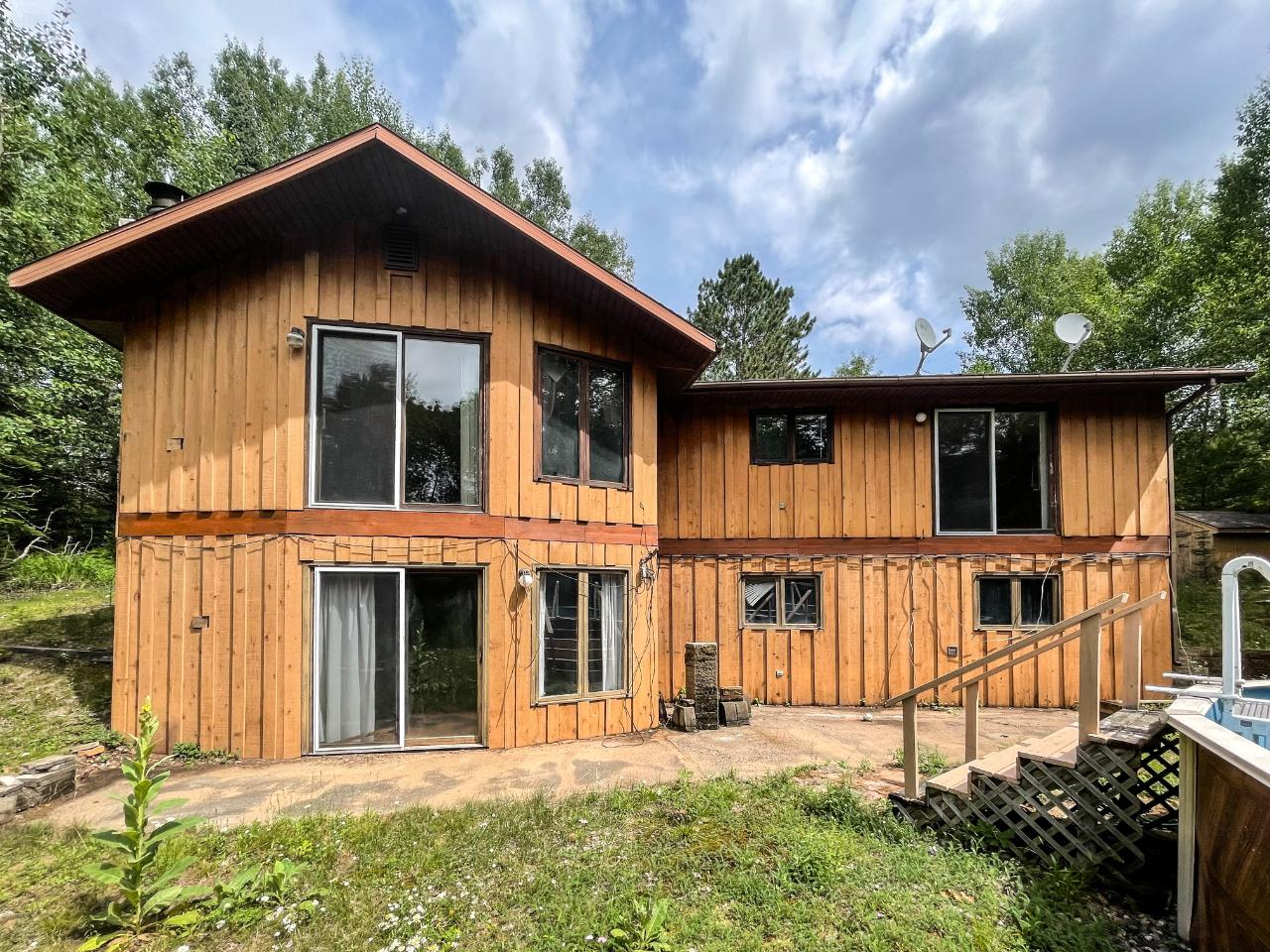 Unique opportunity to purchase a 3-bedroom, 2 bath home w/ off water taxes and a little unknown public access across the road on the Rice River Flowage with sand frontage for swimming or carry in access for paddling on big water. The main level great room offers a wood burning fireplace, large windows and an open concept kitchen and dining area and the entrance to the attached garage. 2 bedrooms and 1 bath upstairs with the master offering a large walk-in closet. The walkout lower level features a rec room with the second wood burning fireplace, an additional bedroom and bath, wet bar and utility room. The patio doors lead you to the concrete patio and complete privacy in your backyard. A little TLC, Exterior paint, decking and elbow grease would allow new owners the opportunity to amplify their equity. Awesome opportunity!