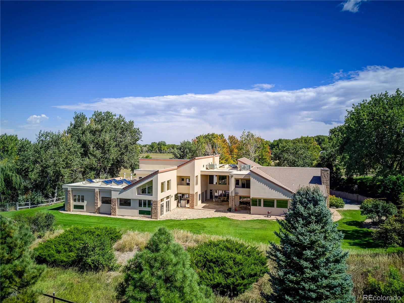Breathtaking mountain views greet you upon entering this one-of-a-kind, 55 acre estate. Opulent Colorado Buffed Stone floors guide you to the main level game room complete with a home theater and wet bar. Continue on to the exercise room boasting a steam shower, tanning room, indoor pool and hot tub. The private spiral staircase leads you to the master suite featuring a luxurious 6 piece bath with a dual head steam shower and jetted tub. Follow the bright hallway lined with large, western facing windows to the secondary bedrooms equipped with en suite baths, large walk in closets, and private balconies. Relax next to a cozy fireplace in one of the numerous private living spaces, or entertain guests in the kitchen outfitted with deluxe Viking & SubZero appliances. Walk outside to the covered patio and expansive backyard. Idyllic horse property complete with water rights, fenced pastures, a private pond, and a barn with individual runs.