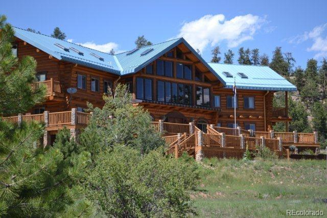 Blue Sky Lodge is ideal for a family or corporate retreat! Sitting proudly in the heart of a magnificent Colorado plateau, it embraces you with a warm welcome and invites your spirit fly! Grand 2-Story Log Lodge w/ snow-capped Pikes Peak Views ~ Impressive Great Room w/ 30+ft Ceilings, Wood Floors &  Fireplace, (4) Bedrooms-all w/ Adjoining Private Baths ~ Gourmet Kitchen ~ Separate Dining ~ (2) Office Areas ~ Large Multi-Level, Wrap-Around Deck Perfect for Entertaining ~ Commercial Water Well ~ Gently Rolling Terrain  ~ High Point w/ 360 Views of Sangre de Cristo's, Pikes Peak, Wright's Reservoir, Mueller State Park, Slater Creek & Fourmile Valley ~ Towering Rock Bluffs
