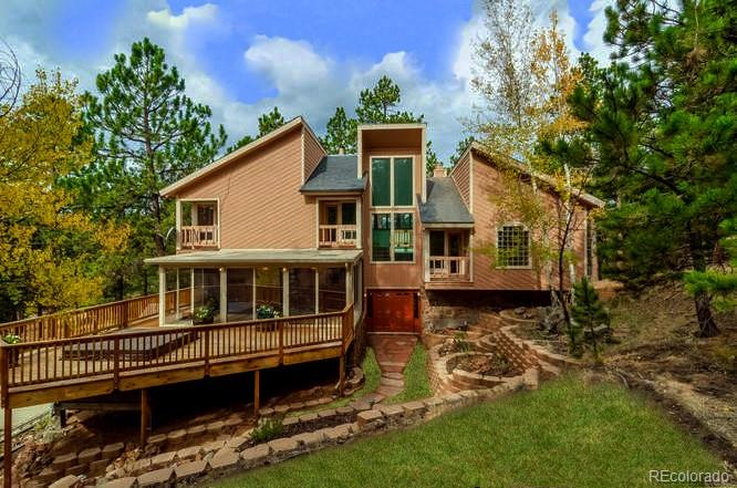 A mountain adventure awaits in this newly updated Woodside beauty.  Lodge design w/dramatic 2 story living rm featuring woodstove & magnificent moss rock gas fireplace.  New carpet thruout.  New exterior paint.  New 590 sq ft deck w/hot tub.  Spacious master bdrm w/5 piece bath including dbl headed walk-in shower, dbl sinks + vanity.  All baths updated.  Lg bright, light remodeled kitchen w/granite counters & oodles of hickory cabs + refinished hw floors.  Cozy fam rm w/gas fp too!  Perfect home for entertaining! Hot water heat for affordable utilities.  Just right mix of trees on 4+ gentle acres.  Extra value in this subdivision w/24+ miles of trails, allows horses w/water users membership & outstanding views.  Convenient commute to Denver yet private & quiet.  Exudes the easy mountain lifestyle.