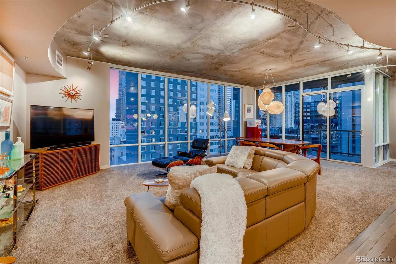 NO HOA DUES FOR A YEAR!! BEAUTIFUL DOWNTOWN VIEWS IN A CORNER HOME! This spacious 2 bed/2.5 bath SPIRE condo has nearly 1,700 sq ft of living space in an open floor plan with floor-to-ceiling glass and tons of natural light. $100,000+ in upgrades include updated kitchen with custom mid-century modern appliances, great lighting, hickory floors & new carpeting, and motorized shades. Fabulous entry, great ceiling fans/lights in bedrooms. Plenty of privacy with 2 bedrooms on opposite ends of the home, each with a dedicated full bathroom. Wonderful oversized balcony. Also included: 1 parking space & storage space in the attached garage. 2nd parking available for purchase. SPIRE is LEED-certified w/40,000 sq ft of amenities: rooftop pool (heated & open year-round), hot-tub, health club, multimedia lounge, home theater, garage dog park, outdoor grilling area, private event lounge, 24-hour courtesy desk, guest suites, modern security & access control systems. SPIRE Denver has super fast 1 Gigabit internet coming soon.