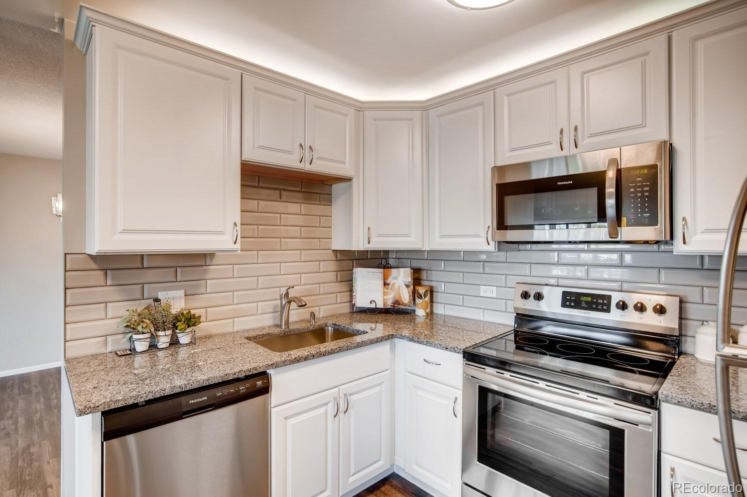 *** Price Slashed on this Beautiful Unit! Similar updated units have sold up to $287,500! ***  Newly Remodeled Kitchen with Lovely White Cabinets, Above Cabinet Lighting, a Beautiful Backsplash and Expanded Slab Granite Countertops with Under-Mount SS Sink! Brand New, Never Been Used Stainless Steel Appliances! The Large Pantry and Beautiful Vinyl Plank Flooring Complete the Kitchen! Enjoy the Grand Open Floorplan with its Expansive Living and Dining Rooms that are Ideal for Entertaining and Comfortable Living! The Huge Master Bedroom Offers a Gigantic Walk-in Closet and a Oversized Private Bathroom! Both Bathrooms have Gorgeous New Vanity Cabinets with Granite Countertops and New Brushed Nickel Fixtures! You'll Love the Gorgeous Plantation Shutters Throughout and the Newer Patio Door that opens to the Large, Carpeted and Enclosed Four Season Lanai! Complete with Updated Modern lighting and New Paint Throughout. This Spacious Home Includes a Huge Finished Storage Room in the Unit Plus another Storage Locker in the building and a Large Storage Box in the Garage as well Making it Easy to Downsize! Completely Move-in Ready!  This Beautifully Remodeled Home is set back from the road and Offers Views of an Expansive Grassy Area with Gorgeous Flower Beds in the Summer! Awesome HOA includes Heat, Water, 24-hour security patrolling, Huge Clubhouse with Indoor & Outdoor Pool, Hot Tub, Sauna, Fitness Center, Lots of Activities, Restaurant and More! There is a 9 hole Par 3 Golf Course and You'll be Close to the Bus Stop Too!