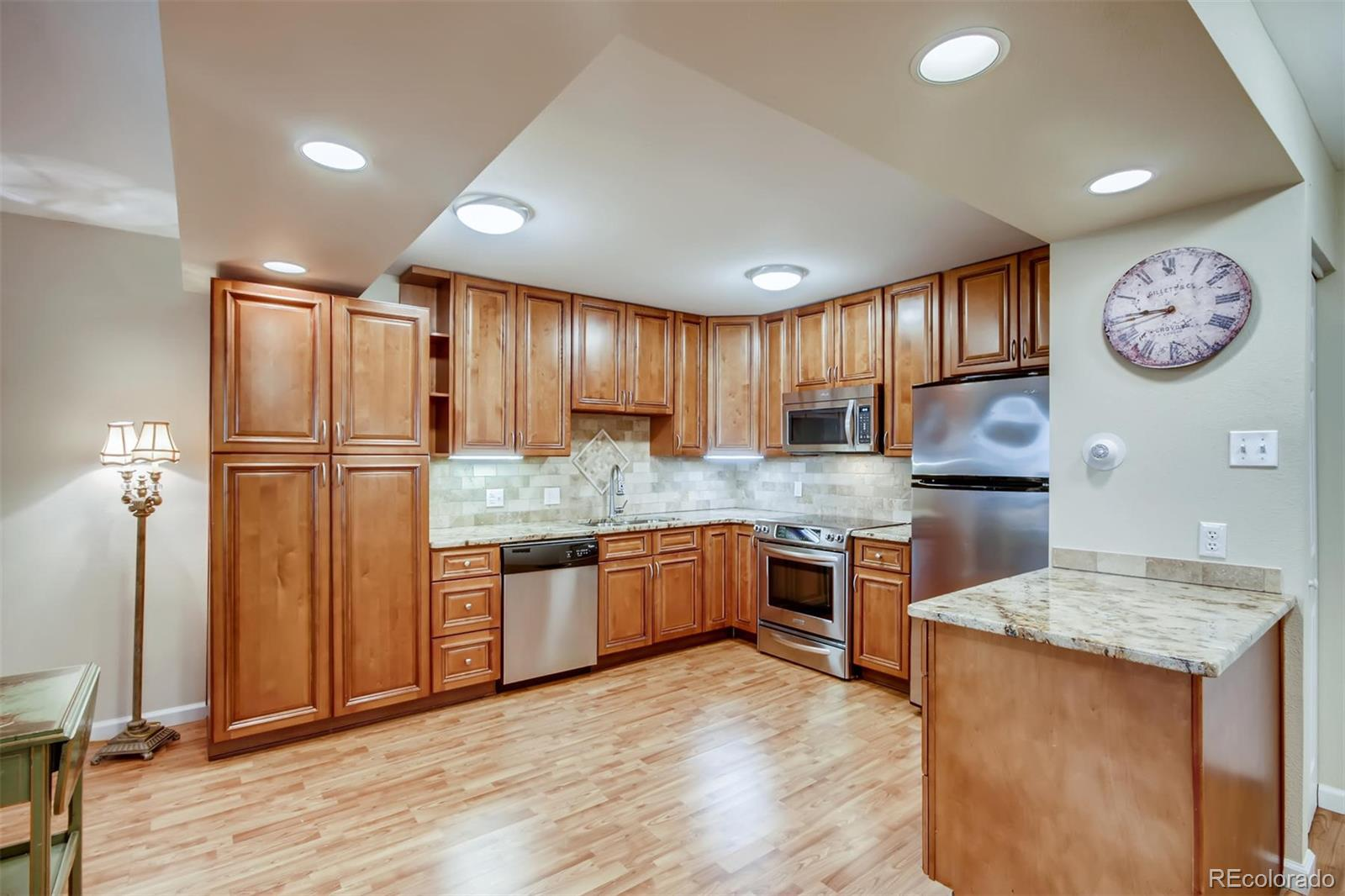 Do not miss the opportunity to own this Remodeled and Sought After first floor condo that is approximately 500 ft from the Community Center.  1200 sf, 2 bedroom,2 bathroom open concept condo.  New air conditioners.  Maple soft-close kitchen & bathroom cabinets with granite counters.  Stainless Appliances.  There is a bonus space by kitchen where you could place a bistro table & 2 chairs or a china cabinet.  Plenty of space in kitchen for dining room table.  Condo comes with underground parking space near elevator.   Antique fireplace with electric flame & heated log unit included.  Large master suite with walk-in closet.  Extra storage closet on 3rd floor in building.  Windsor Gardens is Denver's premier Active 55+ community. At the Community Center you can take dance, glass, ceramic, wood working classes.  Or enjoy the billards room, golfing, library, movie night or live theater.  Public bus in front of building.  Age restricted community.  HOA includes:  Property Taxes, Heat, Water, Sewer, Trash, Recycling, Exterior Maintenance, Snow Removal, Clubhouse, Gym, 2 pools, Underground Parking, Common Area Grounds Maintenance.  Buyer to verify information.Full HOA docs available at www.windsorgardensdenver.org