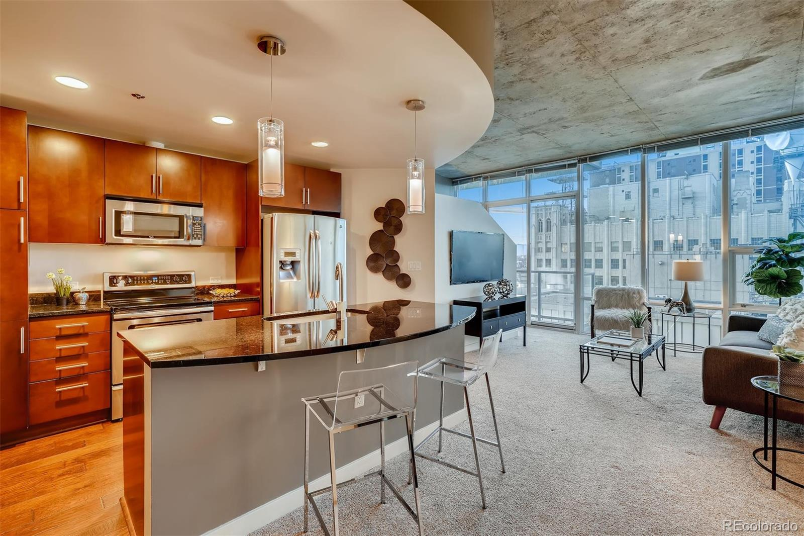 STEP INTO THIS SPIRE CONDO AND WATCH DOWNTOWN DENVER UNFOLD BEFORE YOUR EYES!  This 900 sq. ft. 1-bedroom + den home on the 20th floor of the highly desirable SPIRE building features fantastic floor-to-ceiling windows, a wide-open floor plan, a chef's kitchen with stainless steel appliances and slab granite counters, newer hardwood floors and newer carpeting. From the dedicated balcony, you can enjoy views of Downtown Denver and the Rocky Mountains. Or relax in the master bedroom and gaze at the city views with the nighttime lights. Also included: 1 deeded parking space and 1 storage space in the attached garage. Washer/Dryer included. The 42-story SPIRE is LEED-certified, with 40,000 sq ft of awesome amenities, including a rooftop pool which is heated & open year-round, two hot-tubs, extensive health club, The Zone multimedia lounge, the Box Office multimedia theater, garage dog park, yoga garden, outdoor grilling area, 10th-floor private event lounge, 24-hour courtesy desk, fully-furnished SPIRE guest suites, special accommodations for electric vehicles, and modern security & access control systems. Very well-maintained building! SPIRE Denver has the fast internet coming soon-1 gig dedicated to each condo. Come home to Downtown Denver's SPIRE -- life is better here!