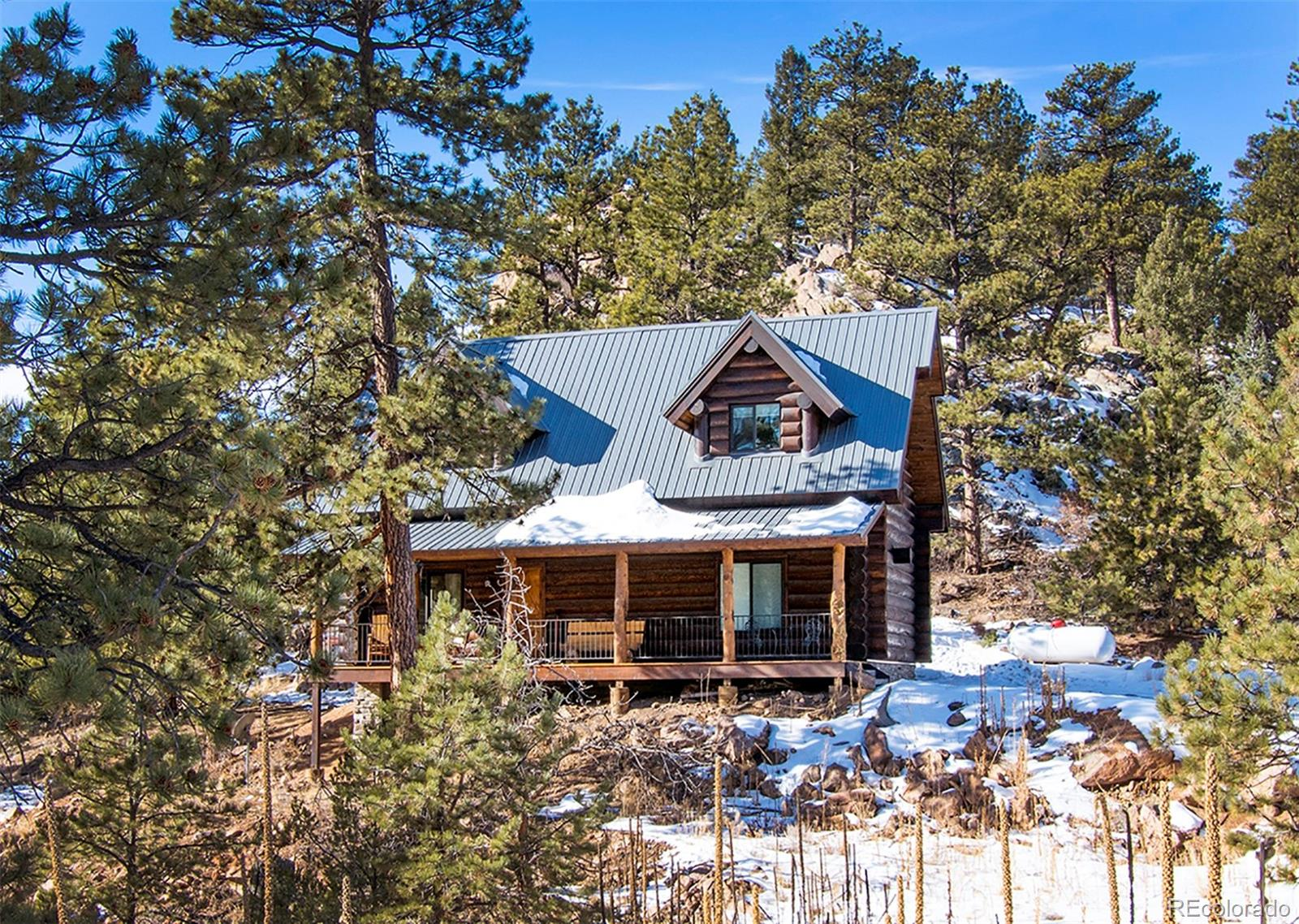 """This amazing log home sitting on over five acres adjoining thousands of acres of BLM was built with quality in mind. This is Colorado living at it's best, adorned with 14"""" pine logs, knotty oak hardwood flooring, custom wood cabinetry, a gorgeous log stairway with wrought iron rails, log interior walls, log beams, tongue and groove ceilings and beetle kill pine finishes.This home offers main level living with open space and gorgeous views from every window. The eat in country kitchen would make any cook happy with ample counter space including steel brushed granite counter tops, stainless steel appliances and a four stool island with butcher block top. The Master Bedroom boasts beautiful views of Mt. Pisgah and a full bath including a claw foot tub and a separate shower with glass surround. Upper level consists of a spacious loft area, two additional bedrooms and a full bath. Sit in the outdoor hot tub and enjoy the silence while surrounded by towering pines and rock formations. Walk to BLM land for some of the best Elk and Mule Deer hunting in Teller County, hiking and all of your recreational fun! Close to Gold Medal fishing and only fifteen minutes to the Historic town of Cripple Creek. RV parking Pad with 220 hook ups!! Great income potential with VRBO or Airbnb. Don't miss this one......"""