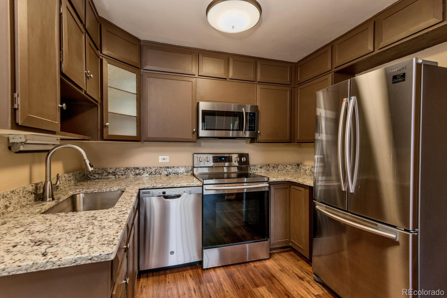 Spacious and updated, this condo is a must see!! Move right in and enjoy this 1380 sf condo in much desired and beautifully maintained Windsor Gardens !!  This condo features 2 bedrooms, 2 bathrooms, plus a bonus den! 2 car underground parking spaces included!!! Great location steps to clubhouse and all the amenities this community has to offer. Kitchen features granite slab countertops, new stainless steel appliances included! Bathrooms with new sinks, faucets and granite slab counters. Laminate wood floors throughout main area- kitchen, entry, and den. Newer neutral paint tones throughout. New Carpet in bedrooms! Master features en-suite 3/4 bathroom, and a large walk-in closet. 3 wall a/c units. Lanai features water resistant laminate flooring, glass/screen enclosure, and 2 vinyl slider doors. Bonus storage room on same floor. Colorado's largest active adult living community, age 55+. FHA/VA approved. HOA Dues include annual property taxes! And also heat, water, sewer, trash, 24-hour patrolling community responders, club house w/indoor & outdoor pool, hot tub, sauna, activities...9 hole par 3 golf course open to the public.