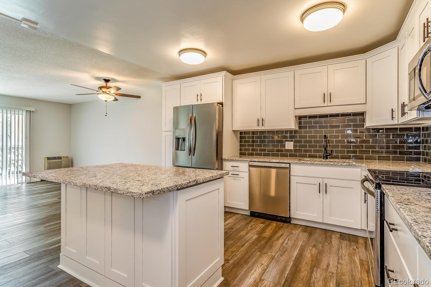 One of the nicest 1st floor remodeled condos- available now! Refreshing and current- this home is 1200 sf, with 2 bedrooms, 2 bathrooms, and 1 detached newer garage w/opener. Kitchen features an abundance of shaker white cabinetry, full stainless appliance package included, bonus island with stool seating, quartz slab countertops, and glass tile backsplash. Bathrooms gorgeous with tall vanities, granite slab counters, and designer tile floor and tub/shower surrounds. Coretec Plus flooring throughout main area, carpet in bedrooms. All new 2 tone paint, baseboards, fixtures, outlets, switches....2 updates wall a/c units. Vinyl Glass/Screen lanai enclosure, and vinyl slider door included. RTD sheltered stop close by. Building is a short walk to the clubhouse and all the amenities. Great opportunity- you do not want to miss this one! Colorado's largest active adult living community, age 55+. FHA/VA approved. HOA Dues include annual property taxes! And also heat, water, sewer, trash, 24-hour patrolling community responder, club house w/indoor & outdoor pool, hot tub, sauna, activities...9 hole par 3 golf course open to the public.