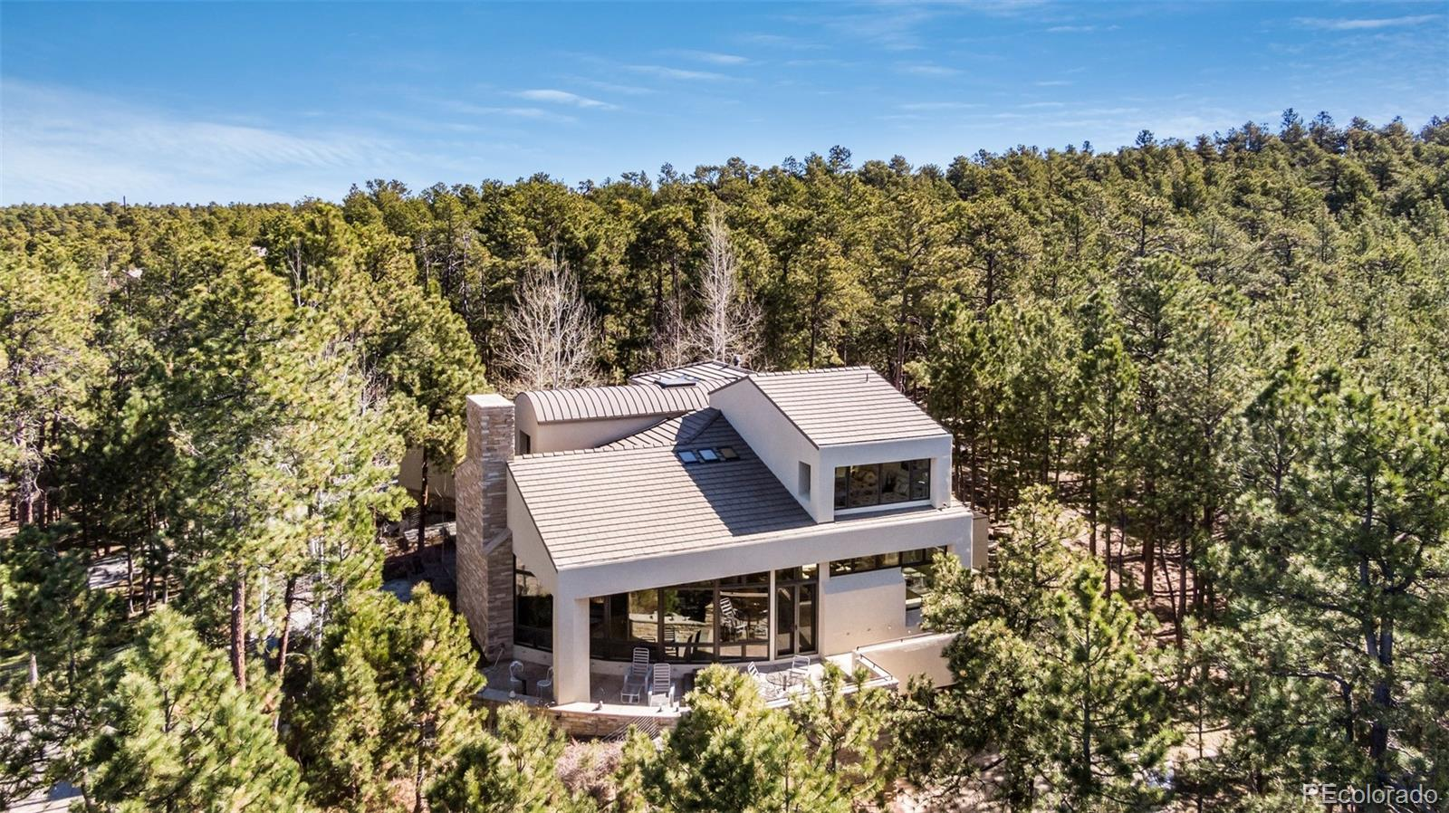 Situated at the end of a cul-de-sac, surrounded by 5 acres of Ponderosa pines and stunning views of Pikes Peak, this 6,276 sq. ft. custom home's inspired architecture blends modern and rustic elements to bring the outdoors in. Craftsmanship and award winning design present in every detail of this 4 bd, 5 ba home. Open concept living with vaulted ceiling, stone fireplace, wall of windows with views of Pikes Peak. Custom eat-in kitchen complete with Ash cabinetry, double oven, convection oven, pantry, island with breakfast bar. Formal dining room boasts a fireplace and built-ins. Second story master retreat includes two sitting areas, see-through fire, five piece bath, and endless views. Walk-out basement has large family room, gym, and 3 additional bedrooms and baths. Perfect for entertaining or relaxing, outdoor seating areas are present on all three levels including wrap around patio with fireplace on main level. 10+ acres of total privacy to the east. Low heating and utility costs, low taxes, and a tiny HOA fee. This spectacular home is only minutes from 1-25, but feels a world away.