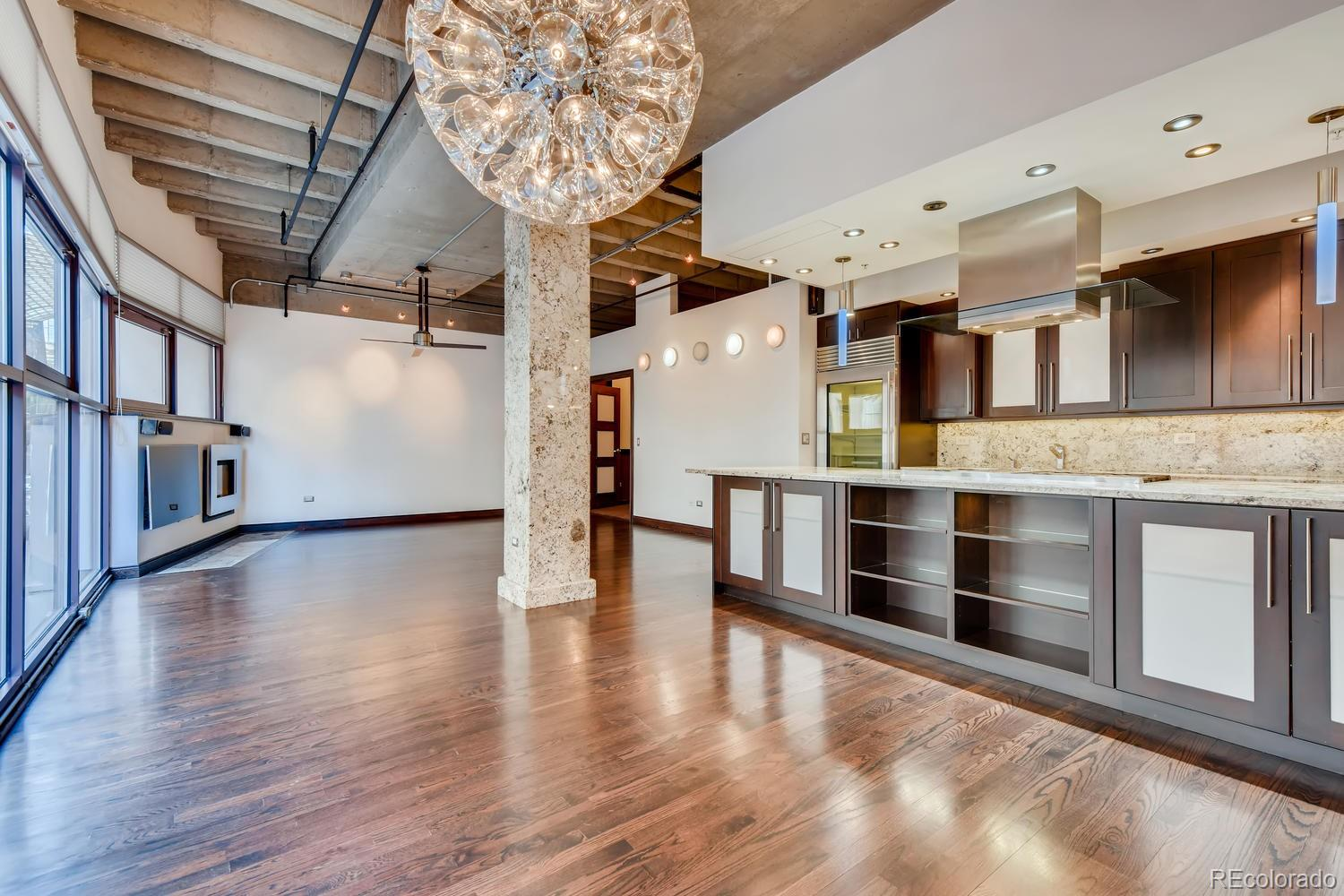 Luxury living in this gorgeous downtown loft. Elements for distancing & comfortable living- you can enter the 2nd floor by secured elevator to the loft section and not the building tower. This unit has a separate Heating & A/C not and is not connected to the main building system, Additionally you can walk up to this residence and not have to use the elevator. Elevators are separate from the main building elevators. The hallway gallery flows into the fabulous kitchen which featuring outstanding appliances- 6 burner+griddle gas range with double oven, wine chiller, drawer refrigerators, Subzero glass door refrigerator, Miele built-in coffee station, warming drawer and Fisher/Paykel dishwasher drawers. Across the hall is a cozy tiled patio to enjoy with city with television and gas stub for outdoor barbecue grill. The open dining and living room area has nice features including a wall of windows, gas fireplace, 14' marble faced column, newer roller blinds and high ceilings. Rare to find downtown is a media room with 3-D projector, screen & glasses and custom lighting. Master bedroom with tall ceilings and skylights, includes custom designed shower & tile, heated floors, multiple shower & rain heads with steam and double sinks.  The central bathroom has a custom design with Venetian Plaster walls, air jetted tub and multiple spray head shower.  There are two addition bedrooms all loft like with tall ceilings.  Lots of extras-additional custom bathroom 3/4 bath with multiple spray heads full size laundry room with custom shelving, all the televisions as installed, Prime parking space #418 is included and there is a large storage close by the unit. Prime walk-able downtown location close to all the excitement of the city.  Close to the 16th Mall & shuttle, Larimer Square, Denver Center for the Performing Arts and a walkable distance to Coors Field or Pepsi Center.