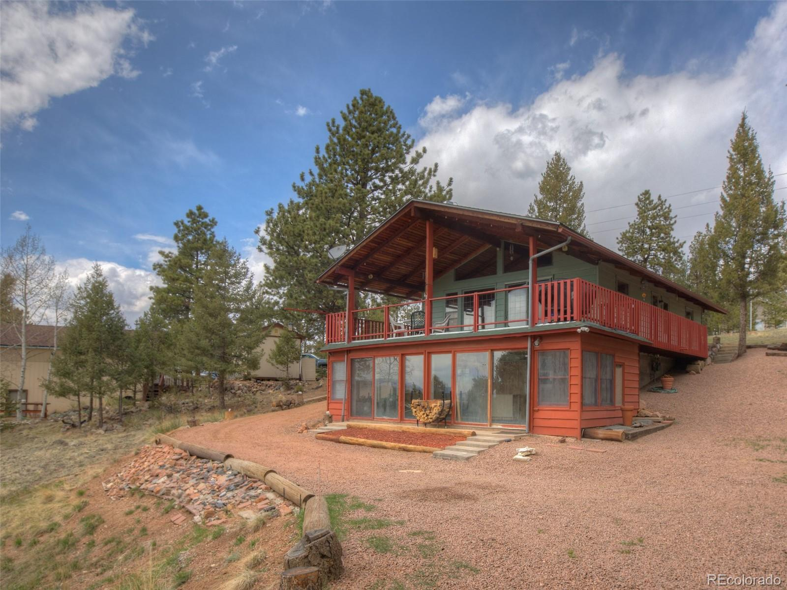 Welcome to your mountain dream home. This amazing rancher sits on 2 lots equaling 1.13 acres and has gorgeous mountain views to enjoy as you sit on the 13 x 30 deck off the kitchen with your family and friends enjoying the outdoors of Colorado. This home is priced to sell quickly and will allow you to add your personal touches to make it your own. The main level as a ¾ bath and large master bedroom with lots of built ins. Vaulted tongue and grove ceiling in the living room that adjoins the kitchen and walk out to the deck. Lower level encompasses a large family room with wood stove and wet bar area along with a full bath, office and open area to make a 2nd bedroom. The best part however is the attached sunroom that keeps the lower level cozy all through the summer and winter months. Great fulltime residence or cabin get-a-way, Welcome Home!