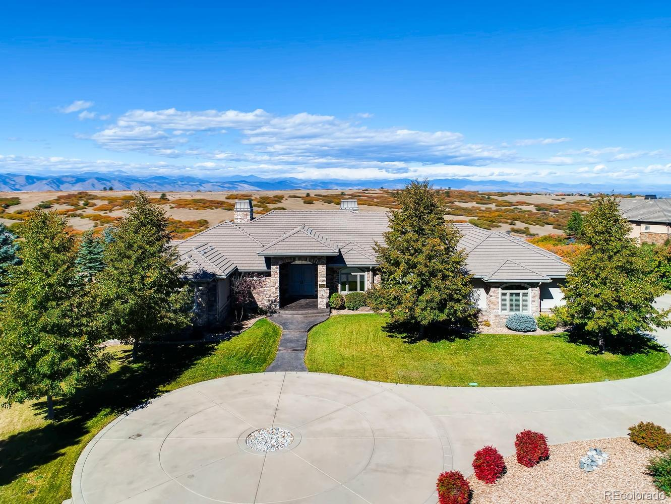 Breathtaking Mountain Views abound on this premium 1.95 acre lot backing to open space and overlooking Daniels Park!  This custom home was designed to provide spectacular views from all the living spaces including the great room, kitchen, nook and master suite. High ceilings and hand troweled walls throughout the home provide an elegant touch. The spacious William Ohs designed kitchen with Wolf and Sub-Zero appliances is laid out perfectly for entertaining. The kitchen nook was created with seamless glass panels to allow stunning unobstructed views of the front range. The great room has hideaway sliding doors that completely open the west wall to the deck, allowing the great room and deck to blend into one seamless entertaining and living space. The back deck spans the entire back of the home and has both covered and uncovered sections to allow you to enjoy the views and outdoors regardless of the weather. Immaculately maintained and ready to move into, but priced to allow you to update to your tastes if preferred!  The comfortable master suite has stunning views of Daniels Park and mountains with access to the back deck.  The lower level has the feel of a walkout with full sized windows, allowing in natural light.  Unfinished space in the lower level allows the possibility for adding another bedroom and bath or adding an additional entertaining area.  The basement also has a separate entrance directly to the garage.  The oversized, heated 3 car garage has an epoxy floor and workspace for the hobbyist. There is space available to add a separate 1400 square foot detached garage for the car enthusiast or RV owner.  The advanced lighting system throughout the home has one touch celestial clock control to provide the perfect ambiance for any situation.  This home was designed with a maintenance free stucco and stone exterior and has a private gated entrance.