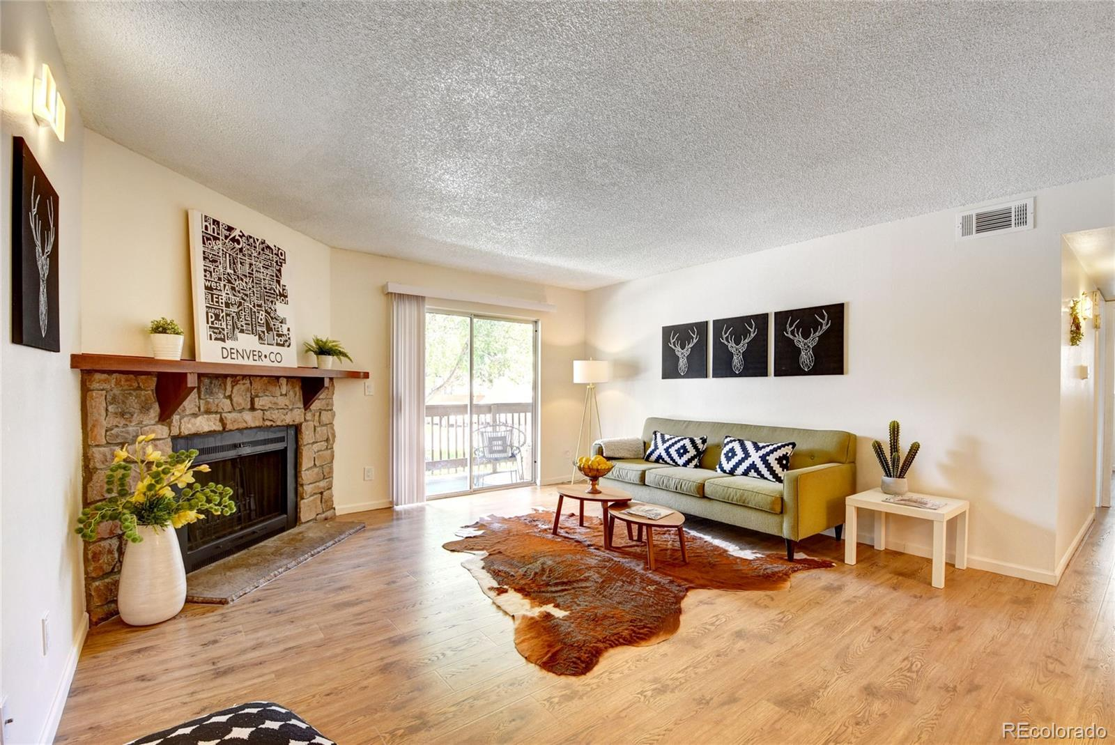 Darling and affordable, farmhouse chic condo located in a central, quiet community. New designer wide plank flooring runs throughout, with new neutral paint, and open-concept living/dining/cooking spaces. Updated kitchen features white kitchen cabinetry, new hardware, black and stainless steel appliances, butcher block laminate counters, and a new iron chandelier in the dining space. Living room offers sliding doors to the covered patio space, and a wood burning fireplace currently functioning with an electric insert. Master suite offers a walk-in closet, and en suite 3/4 bathroom with tiled floors, white and butcher block vanity, newer sink, faucet, and mirror, and tiled shower. True second bedroom has nice closet space and direct access to the patio. The second full bathroom includes a newer sink, faucet and mirror, and a tiled bathtub. Convenient in-unit laundry room features a washer, dryer, and extra storage shelving! Updated light switches and outlets, and regularly maintained HVAC includes a newer thermostat. Reserved parking space #198, plus a private storage unit located off of covered patio. Lots of guest parking available! HOA includes an outdoor pool, clubhouse, snow and trash removal, and grounds maintenance. Easy access to I-225, Nine Mile RTD Station, several bus stops, shopping and several dining options to include Dry Dock Brewing, Tacos El Metate, and Mojo Coffee.