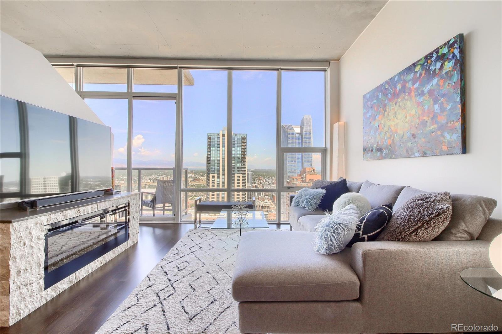 You have arrived! Optimum one and den soaring above Denver's Skyline. Only a select few condo owners in Denver can boast these vast unobstructed mountain and city views.  Large 900 Square foot, modern, open concept one bedroom with additional Den/Flex Space 39 Glorious floors High. When entering, you are immediately drawn to the Wall of Glass, creating a picture-perfect awe-inspiring mountain and cityscape. Rich hardwood floors throughout the main living area of the home. Open concept kitchen/living room and dining leading out to your private balcony perfect for entertaining. Tasteful modern updates like brick wall overlays and fireplaces in both the living room and the master bedroom. The flex space used to be an additional guest bedroom with a bed and a desk. The current owner decided to make it an office only, but the room could easily be used as both office space and guest sleeping quarters.Denver's Premier Address is LEED Certified. Located in the heart of the theatre district next to iconic hotels and restaurants, Performing Arts, Denver Convention Center, the Lightrail, and Much Much More! Enjoy unprecedented amenities spanning over 40,000 square feet!  24/7 concierge, Large Movie Theatre, Business Center. The HUGE Community room takes up nearly the entire floor, including a billiards table, massive viewing screen, wet bar, multiple sitting areas with free WiFi, outdoor grills, hot tubs, and wading pools along with fire pits.  The SkyClub includes wine lockers, billiards table, large flat-screen TV, multiple lounging areas, massive island with seating and food prep area, and private restrooms. Condo fees include nearly all of your utilities along with DirecTV Choice HD w/HBO&Cinemax, 1 Gigabit Internet! Monthly HOA fees fluctuate slightly as a portion is dependent on water, electricity, and steam usage.