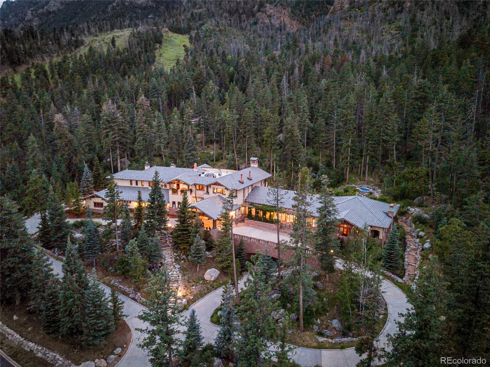Influenced by iconic Craftsman style homes, this dignified estate sits beneath the steep slopes of Cheyenne Mountain. Set in this stunning geologic setting, the intent was to reflect that power in the home's 24,000 square feet. Using granite sourced from the mountain, a mass of boulder creates the foundation, which gives way to brick walls. The brick, hand cast in wood forms, is one of many handmade materials used on the home to connect the setting's raw beauty with human warmth and ingenuity. Completed in 2004, the home's 7 bedrooms, 12 baths & 8 fireplaces showcase work of renowned craftsmen across the country and around the world. at the home's entrance, one is greeted by a grand, redwood timber prte-cohere, designed to invite the mind into another world. Spanning a natural ravine, the house is seamlessly split into two areas, the private north wing & the social/family south wing. With its own entrance, the north wing opens into the home's entrepreneurial headquarters. Here, the workspace is complemented by two bedrooms, a kitchenette, and two baths. Underneath the office, a full apartment, accessible by the garage below, is perfect for staff, guests, visiting consultants, or clientele. An exercise room and sauna link this work area and the home's social/family area. In the south wing of the home, the Renaissance-inspired interior shines with Italian marble underfoot and intricate ceiling finishes overhead. For those who love to entertain or family time, the bar/game room, media room, library/workroom, wine cellar, sports court & pizza oven boast opportunity to enjoy company. Several outdoor terraces offer extensive views. A stone path leads up to the secluded spa. Take a walk among the 500+ acres of trails & open space. The home is an extension of its natural surroundings and yet only five miles to Colorado Springs. The Residence  is intimately scaled and the warmth of textures and fine craft invite one into the long awaited dream of being at home in the woods.