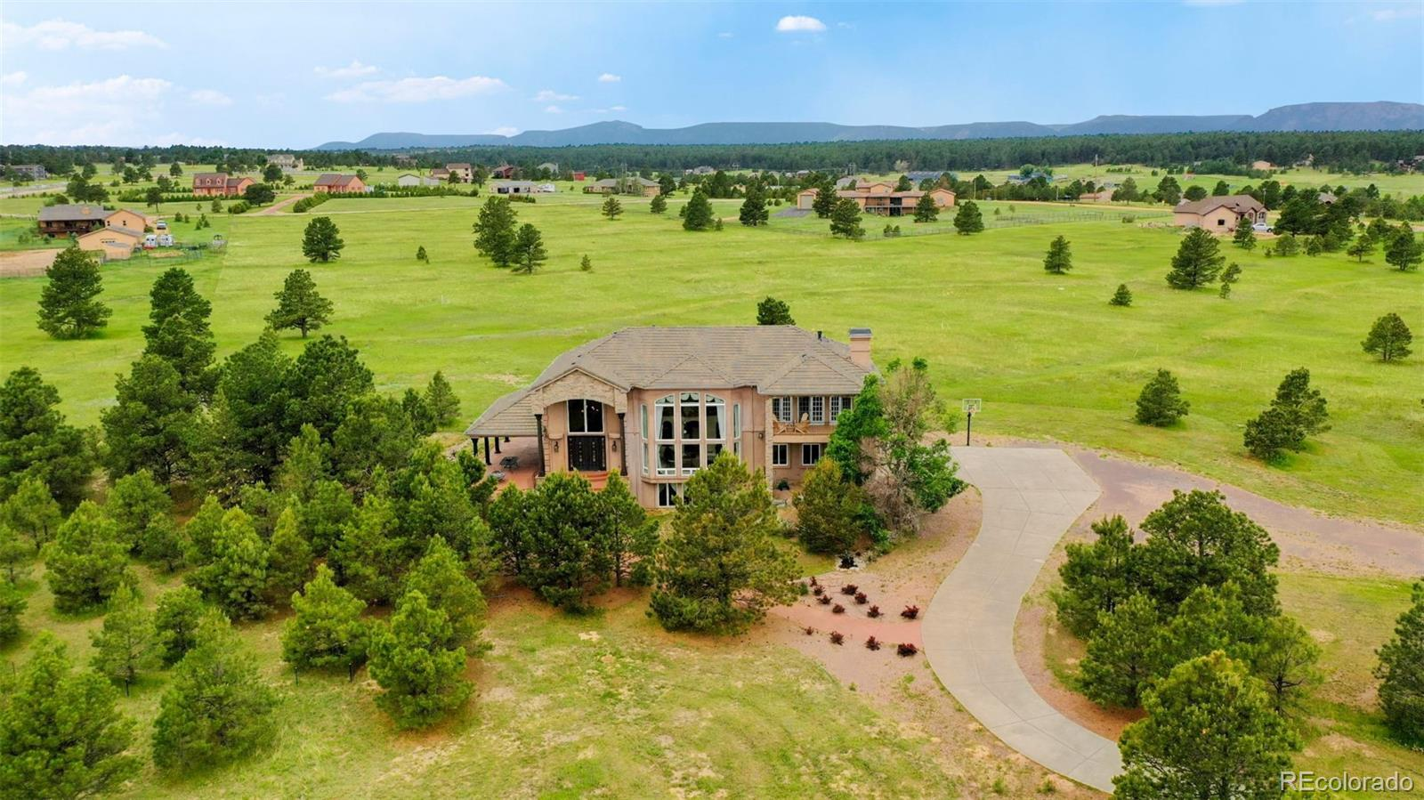 Gorgeous custom estate on 5.22 acres with spectacular views of Pikes Peak from almost every window! Unobstructed views due to large acreage properties to the east and North. Zoned for horses with approximately 6,458 finished square feet with 4 bedrooms and 5 baths. Stunning 2 Story Great Room with magnificent floor to ceiling windows, custom drapes, fireplace and art niches. Amazing attention to detail throughout in the hand-troweled walls/ceilings, Italian marble & hickory hardwood flooring. Luxurious Master Suite with fireplace, en suite spa 5 piece bath with fireplace, heated marble floors, large walk-in closet, 2nd laundry and private 20'x 11' covered deck with outdoor fire pit.  Gourmet kitchen features granite counters, beautiful cabinets, breakfast bar, walk-in pantry and center island. Laundry on main and upper levels. Finished lower level with wet bar, media center, family room/rec room, bath and possible 4th bedroom. 3 decks/patios including a 34'x 16' covered Veranda.