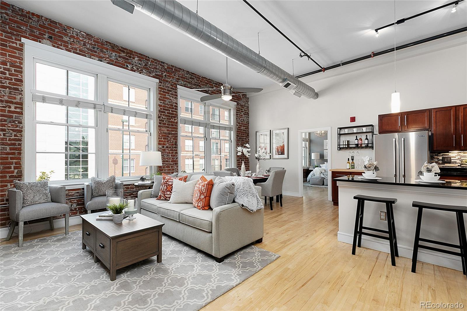 """Beautiful 2 bed/2 bath home in historic Silver State Lofts!  This home also includes a climate-controlled garage parking spot + air rights to build a private rooftop deck above the unit. Entering through the built-in Beetle Kill Pine urban mudroom (organization & shelving), the exposed bricks lead you to the main hearth – over 600 square feet of living area: gourmet kitchen (slab granite, JennAir + Bosch appliances), grand living, dining and custom laundry room – the epitome of livability and convenience.  An owners' wing with oversized master bedroom + brick + windows, attached bath with dual shower + vanity and massive closet are complimented by the second bedroom/office flex place + full bath provide the opportunity to create dual masters specific to this floor plan.  This loft has """"air-rights"""" above, so a private rooftop deck could be your next endeavor – elevating this home to the next level (literally) in the heart of RiNo.  HOA includes 1GB WiFi for the unit and on both rooftops."""