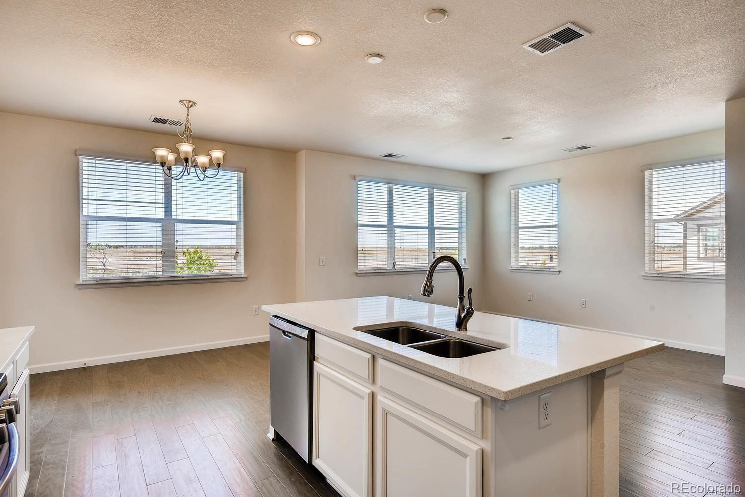 """Stunning 2 bed/ 2 bath in Shadow Canyon on first floor (NO STAIRS). This end unit features an open & bright layout, beautiful white cabinetry, quartz counters throughout, full tile back splash in kitchen & extensive hardwood flooring. The oversized kitchen boasts SS appliances including 5 burner gas range, 42"""" cabinets w/ crown molding & huge kitchen island w/ room for seating. Both Bedrooms are Incredibly spacious and 2 full bathrooms with washer/dryer included. Enjoy the community pool/hot tub, fitness center and club house, just minutes from the unit. 1 Car Detached Garage and reserved parking spot included! Ideally located within walking distance to schools, shopping and restaurants. Book your showing today!"""