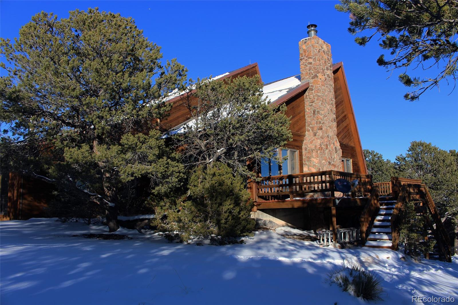 Come check out this custom home in beautiful setting bordering BLM.  This very unique design offers spacious living with high vaulted ceilings and full ground to roof rock fire place.  The master suite is set in a bright sunny room with it's own Kiva fireplace.  There is a oversized garage and 31 x 19 attached shop/studio on the ground floor.  The views from the south facing deck of the Twin Sisters are stunning. There are many hiking trails and places to discover surrounding the property.  Quite, peaceful living at it's best.