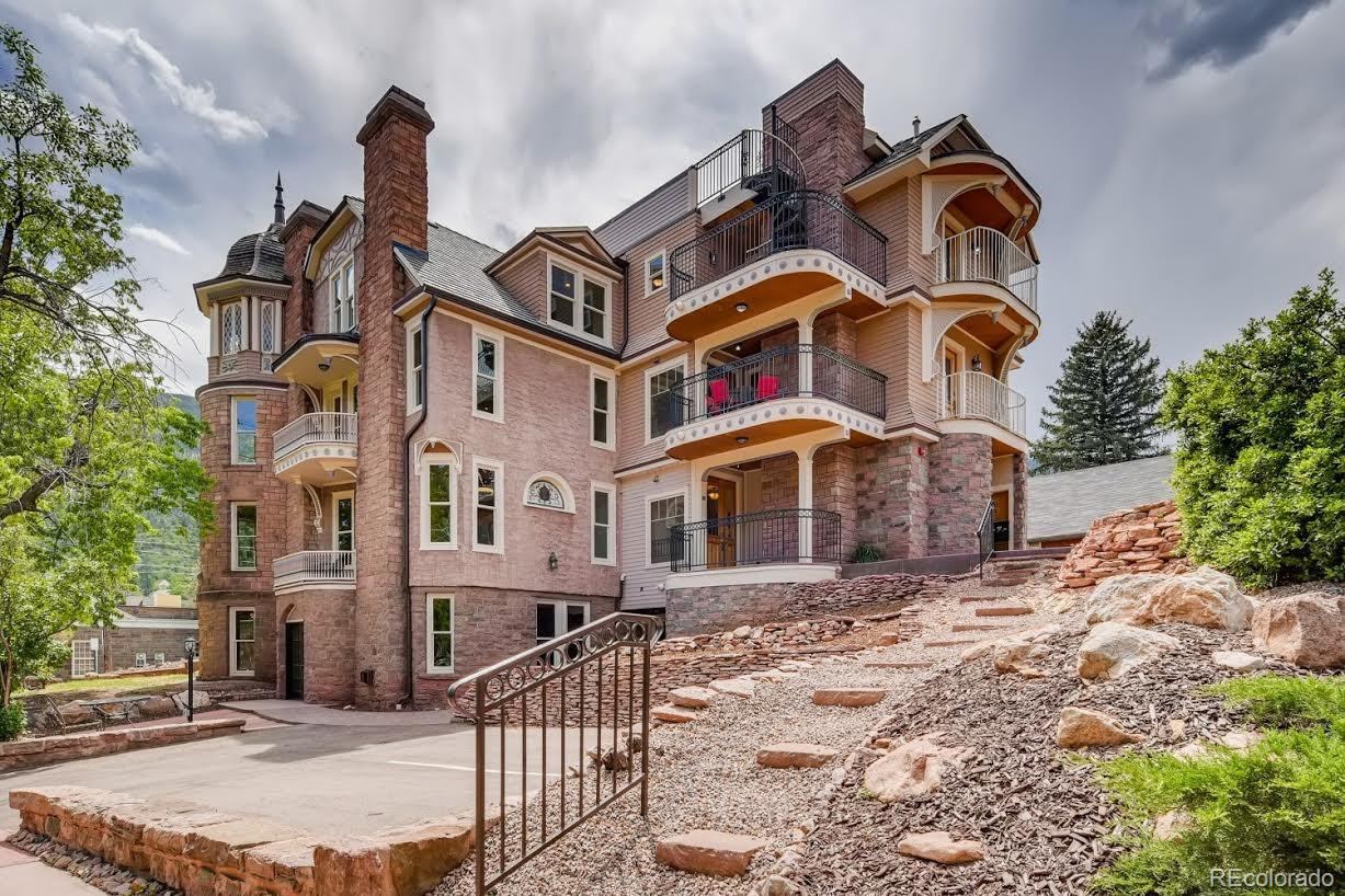 """One level mountain living in 1880 Richardsonian Romanesque. Award Winning renovation ensures modern convenience/historic integrity.   Located in the heart of Manitou, explore hiking/biking trails outside your door.  Stroll to galleries/specialty shops/dining experiences.  Taste mineral springs or join a free-guided tour.   Connect with community opportunities- Mineral Springs Foundation, Open Space, Aquatic Center or civic organizations.  Delight in live music or year round signature events.   Take private elevator to 2nd flr. Handcrafted front door leads into sunlight rooms w/crown molding/baseboards and patterned marble floor.  Two original fireplaces w/inserts grace the living room and master bedroom which share a balcony. Dine in turret room, dining area or at the breakfast bar.  BBQ outside on the deck or relax/enjoy city/mountain views w/coffee or wine from 1 of 2 balconies.  Gourmet kitchen features picture window of Manitou, granite counters, Kitchen Aid Pro SS Appliances, 6 burner gas stove/griddle/pot filler, 36"""" French door refrigerator, microwave/convection wall ovens, 36"""" farm sink, dishwasher, instant hot water, beverage/wine cooler and slow close cabinets. Invisidoors conceal laundry area, muffling operating units.    Master bathroom features marble shower w/Delta fixtures, Kohler comfort height toilet, hardwood bathroom vanities, solid tops, matching mirrors.   Radiant heating, soundproofing, On Demand hot water, MicroSplit AC, LED lighting, Centralized Media Center, In House vacuum w/Vacusweep. A back entrance to designated parking.  HOA equals maintenance free exterior.   Come home to Manitou Springs! Virtual staging was used in some photos."""