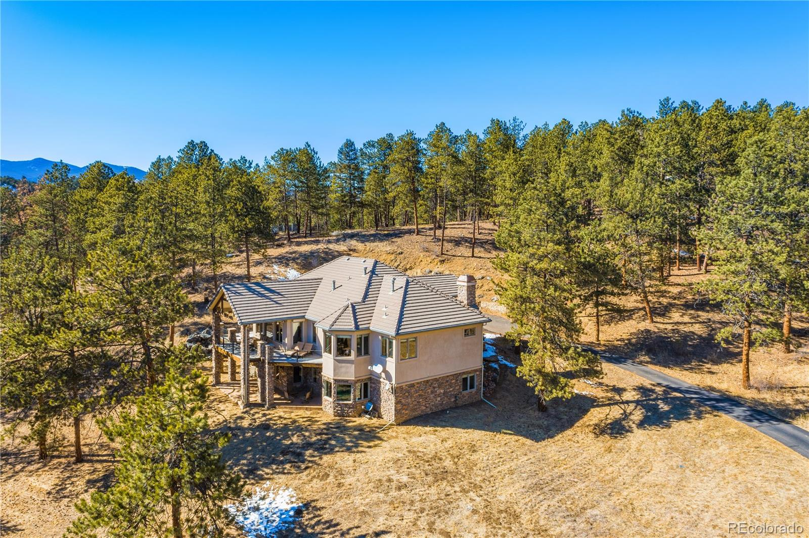 "Wow! Locations like this don't come around very often. Secluded on 15 wooded acres yet close to shopping, restaurants and trails! Unmatched location, 25 minutes to Downtown Denver and just 40 minutes to Loveland Ski Resort. Amazing top-notch Evergreen schools. The home has easy access year-round with a paved road and driveway that leads all the way to property right off US40. Custom Kinsey Griffin sprawling ranch with a massive deck, hand-troweled walls, vaulted ceilings and oversized windows maximizing the home's setting and surroundings. Private main floor master boasts its own rear deck access, 10ft ceilings, oversized walk-in closet, 5-piece spa bathroom w/ dual-sided fireplace and jacuzzi tub. The wide-open floorplan combines an oversized vaulted family room, a gourmet kitchen with 42"" custom cabinets, granite countertops, Thermador 6-burner gas range, Sub Zero built-in fridge, and large walk-in pantry. Main floor office with its own private fireplace. The open staircase leads to a functional walkout basement with 3 private bedrooms all with walk-in closets, 2 of the rooms share a Jack & Jill and the 3rd bedroom ensuite, last but not least an open 1/2 bath for those you entertain. The large home theater and nearby wetbar can be a fantastic way to bring everyone together! The basement also has a secondary stairway! Outside is a playground on the property with getaways including a trampoline, an area for a zip line."