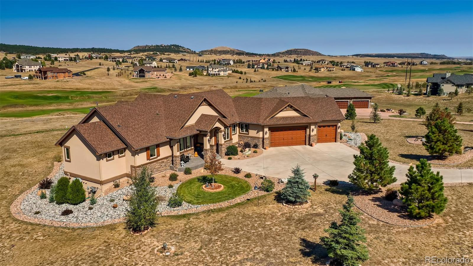 Stunning Custom Home built to the highest standards, you will enjoy Main Floor Living located on a quiet cul-de-sac, situated on 2.5 acres overlooking the King's Deer Golf Course where you can enjoy 18 holes with amazing Pikes Peak & Front Range views. The Sundance model is a Warm and Open floor Plan with dramatic vaulted ceilings, arches, and beams perfect for the most discerning Buyer. Hardwood throughout the main floor, 5 Bedrooms, 5 Baths, 3 Car Oversized Gar. The Chef will love the Spacious well-appointed Gourmet Kitchen, complete with Granite slab countertops, GE stainless steel appl, Gas Cooktop, Walk-through Pantry. Kitchen opens to the warm and inviting Great Rm keeping you connected to the family, the Vaulted Ceilings, Faux Timber Beams, Abundant Light & 2-Story Stone Fireplace make it cozy & inviting. Walk out to your Vaulted Covered Composite Deck, to enjoy the Mountain & Golf Course Views. Gather around the table in the elegant Formal Dining Room with custom features like Crown Molding, Ambient Lighting, and 10' Ceilings. On to the Master where you will feel like Royalty, featuring Vaulted Ceilings, Dbl-Sided FP, & a massive Walk-in-Closet. Step into the Luxurious Master 5-Piece Ba w/Radiant Heated Tile Floors, Huge Walk-in Double Head Zero Entry Euro Shower, His & Her Sinks, & Soaking Tub w/a FP. Utilize one of the main floor Bedrms as an office w/a ¾ bath across the hall. Guests can enjoy a Jr. Suite w/En-Suite Bathroom & walk-in-closet. Enter from the 3-car oversized gar to the bright Daylight Mudrm & Laundry Rm. The Fin Bsmt is an Entertainers Dream with a custom Wet Bar, Media/Home Theater Rm, Game/Pool Table Area, Family Rm that walks out to the Covered Patio to enjoy Panoramic Views, & a beautifully landscaped yard.  The Lower level has an additional 2 Bedrms, 2 Baths & plenty of Storage Space including a Vault & future planned Elevator area (with a Poured Slab). This Gorgeous Retreat will not last long, make it yours today!
