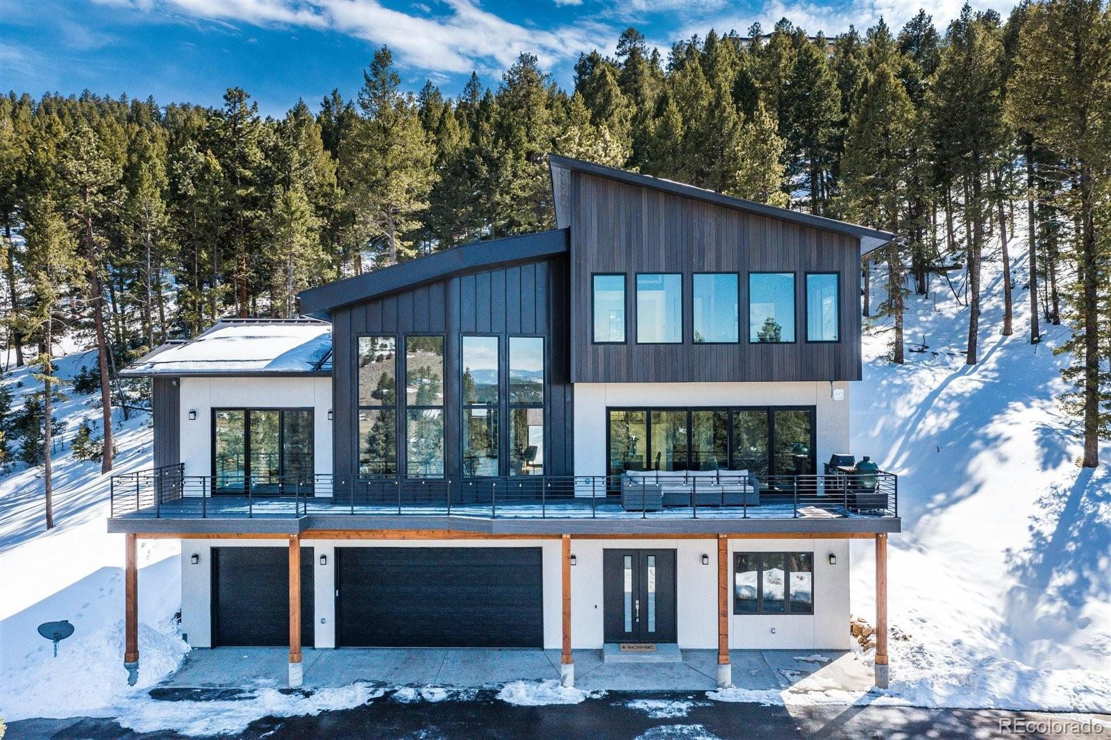 """A magnificent mountain vista w/ custom designed high-end finishes, spectacular views, & only 7 min to downtown Evergreen! Enter the front doors & walk into a lobby w/ soaring ceilings & modern light fixtures. This lower level has a den (great workout room or additional office), a full bathroom & a perfect guest w/ a good size storage closet. Head up to the main level & you will be wowed instantly by the spectacular great room! With floor to ceiling windows & an impressive center gas log fireplace w/ inset chopped wood, this space is beyond impressive. The open floor plan connects the dining room & the gourmet kitchen w/ high & Bosch appliances, a coffee/wine bar & unique granite island. One of this home's greatest features is the access to the outdoors. The 5 panel glass doors from the kitchen & dining slide back fully, creating a natural flow from the large deck into the main living space. Enjoy cookouts w/ your outdoor kitchen w/ grill, mini fridge, & smoker. The main level also consists of an office w/ built-in desk & full bathroom. The large laundry room attaches to the walk-in pantry & opens to the back patio w/ hookups for a hot tub. The main level master bedroom also has direct access to the deck. The spa-like master 5-piece bathroom has a large shower, freestanding soaking tub & walk-in closet. Upstairs you will find 2 additional bedrooms, perfect for """"bunk"""" or guest rooms, & a full bathroom. The upper loft in this home is the true showstopper w/ panoramic views of snow capped mountains. This is a great theater or party room. The home is complete w/ a 3 car garage w/ heated floors & pre-plumbed for a utility sink or dog wash. Additional features: public water & sewer, NETEO high-speed internet, DirecTV & StarLink, snow/gutter guards, surround sound speakers, & $125,000 worth of hardscaping, ready to add your landscaping touches! Enjoy all Evergreen has to offer in just minutes or commute to Denver in 30-45 minutes. The perfect """"near everything"""" mountain home"""