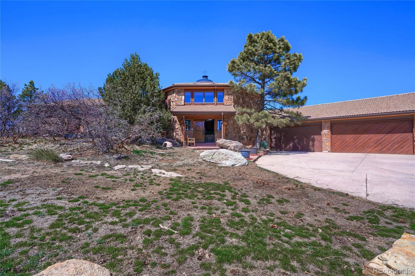 Stunning fully custom built home with separate guest house and barn sitting on just under 6 acres with amazing views of the front range and no one behind you to block your view!  This property has a country feel but is just minutes away from I-25 with easy access to Denver and Castle Rock.  Walk right in the main home and find yourself in the great room with over 20 foot tongue and groove wood walls and ceiling and solid wood beams! Find the library with amazing mountain views in the back right of the great room by walking up the solid wood spiral staircase.  Recently remodeled, the kitchen features stainless steel Wolf appliances, beautiful granite countertops with kitchen island and breakfast bar seating, heated tile flooring and an amazing built in garden feature!  The master bedroom is situated perfectly to take full advantage of the front range views and has a door leading out to the hot tub on the back deck for evening soaking!  Master bathroom includes a granite countertop double vanity, walk-in live steam shower with live moss rock and dual shower heads!  Walk out to the spacious backyard and you will find a large three level deck.  The lower level is the largest with plenty of room for your outdoor furniture, take a few steps up to find the built-in hot tub where you can watch the sunset over the mountains or walk up to the top deck to really get a great 180 degree view of Denver down to Castle Rock and everything in between.  Four car garage heated and insulated with a large workshop attached.  The guest house is a 2 bed/2 bath one level home sitting on top of a 2400 sq ft heated barn area.  This home could easily be transformed into a 3 bed/3 bath home if needed as plumbing is already there for it.  Located high on a ridge in the perfect location to feel like you are away from the hustle and bustle of it all but yet just minutes away from everything Castle Rock and Lone Tree have to offer. Come take a look, you don't want to miss it.