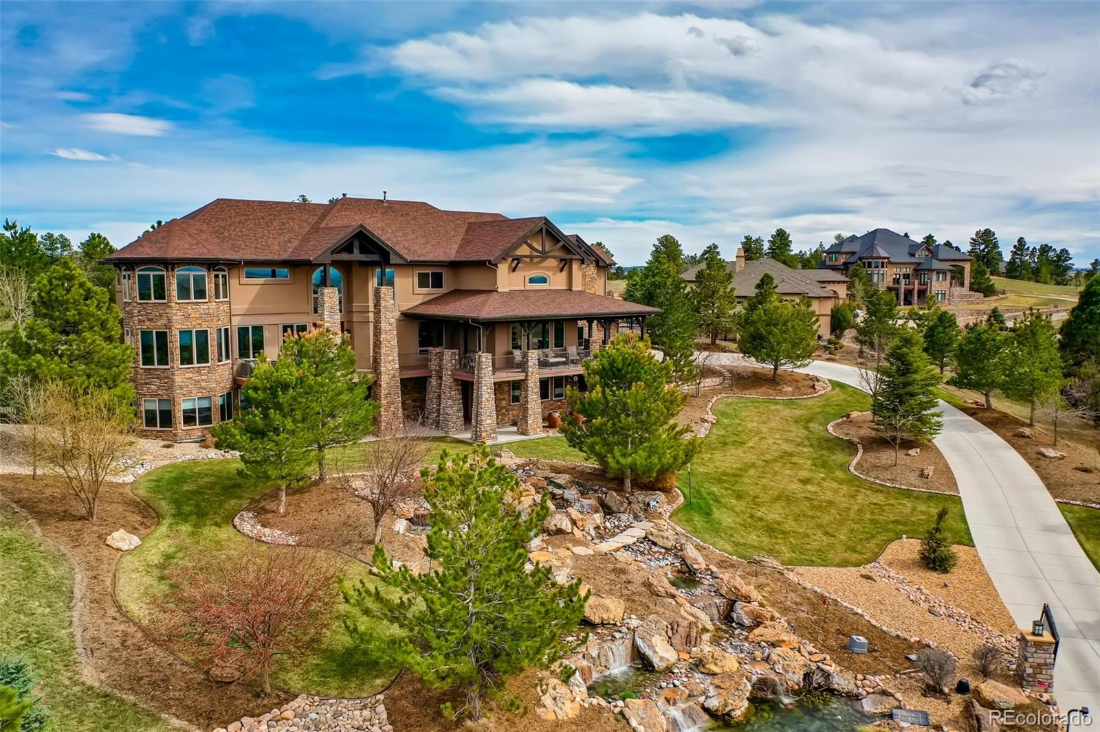 "Colorado luxury defined with extraordinary architectural details and magnificent mountain views from all three levels. Located in a quiet cul-de-sac in the heart of the exclusive Timbers at the Pinery neighborhood; this outdoor oasis sits atop an elevated 1.49 acre lot with an impressive cascading water feature, whispering pines, & in-ground hot tub with water fall. The kitchen, breakfast room, & great room create the heart & soul of the home. A gourmet kitchen w/ large slab granite island, Dacor & Wolf appliances, alder cabinetry features a wet bar, prep-station, ice maker, butler's pantry, built-in refrigerator, & breakfast bar. Gorgeous Great Room w/ striking stone fireplace ascending to the timber-trussed ceiling & custom built-in's.  The main level features, one of two laundry rooms, well appointed formal dining room, & home office w/ custom wood work, built-in's & private outdoor patio.  Upper level features a generous master retreat w/ spectacular mtn views, luxury sitting area, fireplace for romantic evenings, elegant 5-piece master bath w/ French doors, heated tile floors, walk-through shower, jetted tub, dual sinks & impressive walk-in closet.  Three additional bedrooms each w/ walk-in closets & private bathrooms, Upper Laundry & Loft complete the upper level. The show-stopping walkout level boasts a Family room w/ stone fireplace, impressive wet bar w/ full sized fridge, hidden bar TV, trash compactor, dishwasher, dual tap kegerator, ice maker & island w/ granite counters & bar seating, Game Room w/ built-in leather couch, retractable TV, & aquarium, Media Room w/ 8 person stadium seating, 120"" screen, & surround sound, Wine Cellar w/ wood barrel ceiling previously featured in Architectural Digest, & 5th bedroom, 3/4 bath complete the lower level.  Enjoy custom tech features; Control4, JellyFish Outdoor Lighting, & Nest Thermostat. Outside enjoy the covered patio with outdoor kitchen, natural gas grill, mini fridge and destination patio with gas fire pit."