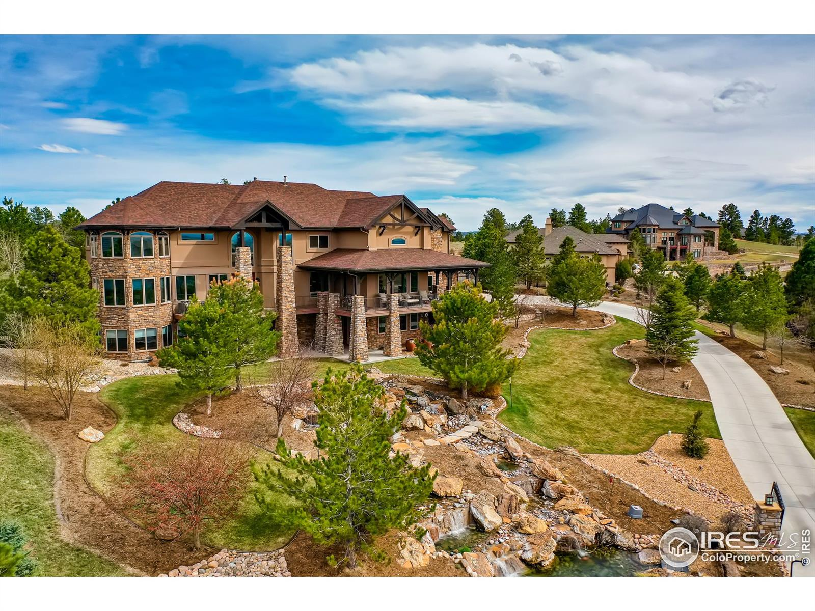 "Colorado luxury defined with extraordinary architectural details and magnificent mountain views from all three levels. Located in a quiet cul-de-sac in the heart of the exclusive Timbers at the Pinery neighborhood; this outdoor oasis sits atop an elevated 1.49 acre lot with an impressive cascading water feature, whispering pines, & in-ground hot tub with water fall. The kitchen, breakfast room, & great room create the heart & soul of the home. Gorgeous Great Room w/ striking stone fireplace ascending to the timber-trussed ceiling & custom built-in's. Upper level features a generous master retreat w/ spectacular mtn views, luxury sitting area, fireplace for romantic evenings, elegant 5-piece master bath. The show-stopping walkout level boasts a Family room w/ stone fireplace, Game Room w/ built-in leather couch, retractable TV, & aquarium, Media Room w/ 8 person stadium seating, 120"" screen, & surround sound, Wine Cellar w/ wood barrel ceiling featured in Architectural Digest."