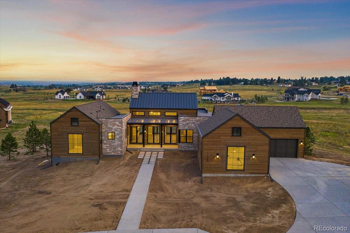 """The """"Landon"""" by Nicholas Custom Homes is a Colorado modern farmhouse re-imagined and a featured home in the 2021 Fox Hill Custom Home Showcase! Appointed on 1.58 acres, the Landon is positioned along a cul-de-sac, backs to dedicated open space and is arranged to take in the beautiful Colorado mountain views. The 5 bed, 6 bath design includes 4,297 finished square feet, and oversized four car garage and the coveted 1,156 sqft barn style outbuilding! The covered front porch opens into a spacious vaulted great room with beams, grand fireplace, triple French doors to an uncovered patio space, dedicated study, open-concept kitchen with luxury appliances, bright and spacious eat-in space with not one, but two outdoor dining and entertaining spaces connected to the dining space. A main floor guest room suite and main floor master retreat with coffered ceilings, expansive front range views, owner's master spa bathroom and oversized walk-in closet complete the main floor. The lower level features a spacious recreational room with fireplace, two en-suite bedrooms, a flex space for your workout room or optional 5th bedroom, wet bar and walk-out access to the landscaped yard and open space – this house has been intentionally and methodically designed. The spacious and over-sized four-car garage with additional storage space and the coveted custom outbuilding make this home a unique and truly turn-key custom home to enhance your farm-to-table lifestyle at Fox Hill!"""