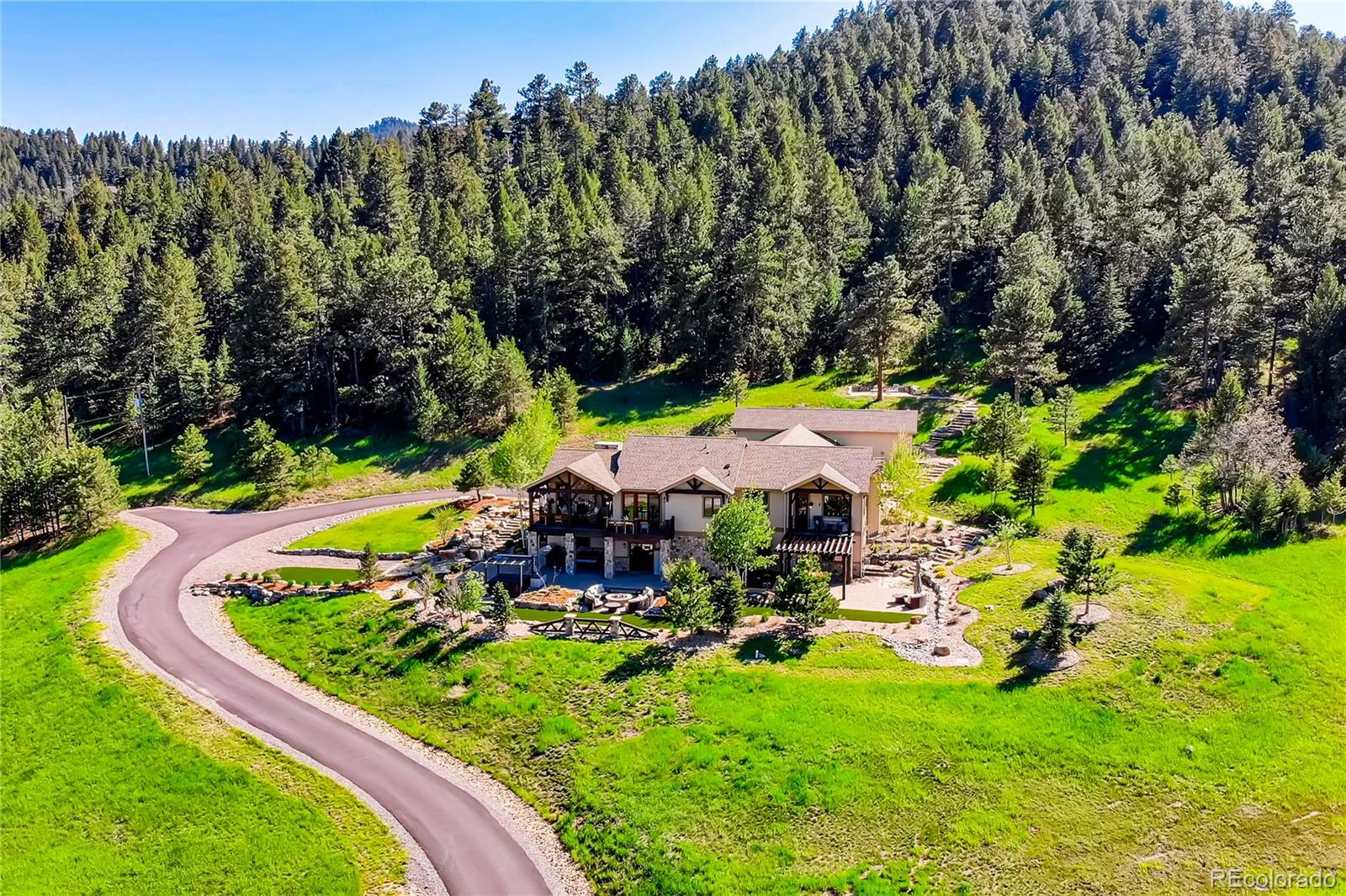 CHECK OUT DRONE VIDEO BY CLICKING ON THE VIDEO REEL or HOMESNAP-virtual tour under photos!  Stunning hillside Luxury home on 5 acres where mountain meets meadow in the highly sought after Lane Ranch neighborhood of Indian Hills offering 360 degree mountain views to enjoy the stunning Colorado sunsets. Modern Mountain living w/ paved roads, natural gas, XFINITY WIFI (only home in Lane Ranch w/ xfinity) and Mountain views you don't want to miss! As you enter, soaring vaulted ceilings highlight the open, Colorado architectural design with big living spaces. Clean lines & elegant finishes define this luxury home. Exquisite private master suite and 3 en suite bedrooms, open kitchen with expansive granite countertops, dining and hearth room concept that overlook the deck, fire pit, built-in kitchenette and hot tub which hear the soothing sounds of the top of the line water feature. Oversized 3-car heated garage and bonus RV garage w/ full hookups, 50A power, water & sewer, finished basement w/ built in speaker system, fenced dog run and additional storage areas provide more than enough room for cars, boats, toys and all the gear your mountain lifestyle will desire. Top-notch landscaping comprising over 120 tons of rock, this outside oasis is full of features that are perfect for a quiet evening outdoors or entertaining family and friends. Stone stairways take you around the entire home and to an upper seating area to enjoy a nice mid afternoon siesta in the fresh mountain air.  This home features two luxurious outdoor patios running the length of the home with an under deck drainage system and a private master suite patio. The privacy of this home and abundance of nature and wildlife is second to none.  Enjoy the solitude of foothill living just 35 minutes from downtown Denver yet w/in minutes of vast trail systems such as Red Rocks Amphitheater, Parmalee Gulch Park, and Mt. Falcon. A must see for those wanting contemporary mountain living but short drive to the city!