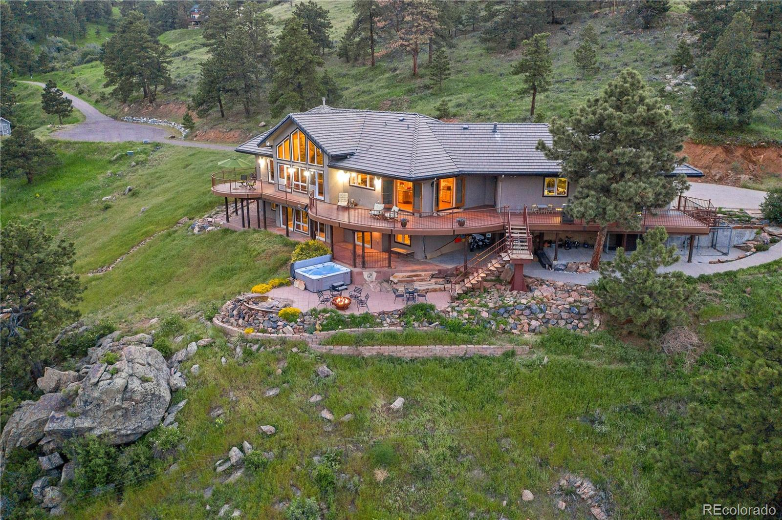 Escape to this stunning retreat on Lookout Mountain! Less than 30 minutes from Downtown Denver, you can enjoy this private, serene setting with panoramic views. Explore 6.46 acres surrounded by Apex Park/Jefferson County Open Space, which has 9.5 miles of hiking trails on 697 acres.  Tranquil scenery as you enter the front door.  Open all the french doors and breathe the fresh mountain air.  Gather around the kitchen island and take in the city lights and trees for miles.  Kitchen is complete with custom Alder cabinetry, granite counters, double ovens, Dacor gas range with griddle, wine fridge, and coffee bar.  Expansive wrap-around deck with a natural gas grill with room to relax and entertain.  Custom stone stairs lead to a hot tub, water feature and natural gas fire pit.  Large pantry/mudroom with custom shelves.  Cozy dining room perfect for entertaining.  Gorgeous stone fireplace.  Main floor laundry/craft room.  Guest suite with a gas fireplace, private full bath and huge walk-in closet.  Grand master suite with sitting area and custom his/hers Elfa closet.  Enjoy the outside water feature from the 5 piece bath with a  jetted tub.  The lower level has more french doors to walk-out and enjoy the views.  The bar area has a full refrigerator, wall oven, microwave, dishwasher and pool table.  Relax in the cozy living room in front of the gas fireplace.  Climate-controlled wine room with bistro table.  Huge exercise room.  2 large bedrooms with a large bathroom.  Extra storage.  New water heaters.  Peaceful views from every window.  Playground area with swing set and slide.  Special RV parking up by the pond just past the shed.  Be sure to check out the video tour.  The mountains are calling!