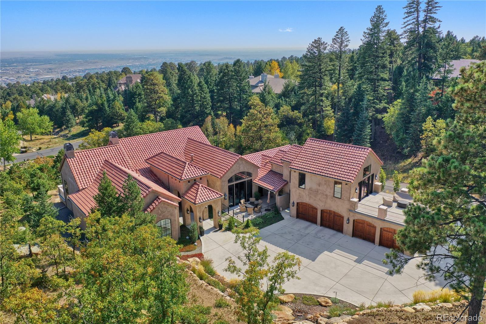 Custom built w/majestic mountain & city views. Special features include wide-plank hardwood floors on the main & upper level; solid alder doors; beamed peaked ceilings; crown moldings; 5 patios w/a total of 3,282 square feet; amazing light fixtures (some antique & vintage);all bedrooms are en-suite; incredible landscaping w/18' waterfall; private office on upper level has full bath & a private view patio that overlooks the waterfall; wine cellar w/bricked beamed ceiling & wrought iron entry doors. The focal point of the home is the stunning great room that features a beamed peaked ceiling, massive stone fireplace & 4 sets of French doors that access the back veranda to a majestic city view. Adjoining the great room, the gourmet kitchen features a big center isle w/seating, slab granite counters, extra-large walk-in pantry & a professional grade gas stove w/two ovens & a gas cooktop w/10 burners! Other kitchen appliances include 2 dishwashers, wine fridge, stand-alone freezer, stand-alone refrigerator, pot-filler & ice maker. The kitchen opens to a cozy hearth area that accesses the front courtyard w/majestic mountain views. The luxurious main level master opens to the back veranda & 12' ceilings w/crown molding, lovely fireplace w/gas logs & a huge walk-in closet w/two designer chandeliers. The sumptuous master bath enjoys slab granite countertops, an oversized shower w/2 shower heads & marble bench, jetted tub & a beverage station w/sink & fridge. The main level laundry room comes complete w/a computer work station, slab marble counters & a refurbished antique chandelier. The walkout lower has 10' ceilings & features a big family room w/fireplace, wet bar & the amazing wine cellar. The lower level has three spacious guest bedroom suites. All of these bedrooms open to a patio & all have private baths & walk-in closets. Custom window treatments throughout! 578 sq. ft. in the upper office is included in the main level square footage.