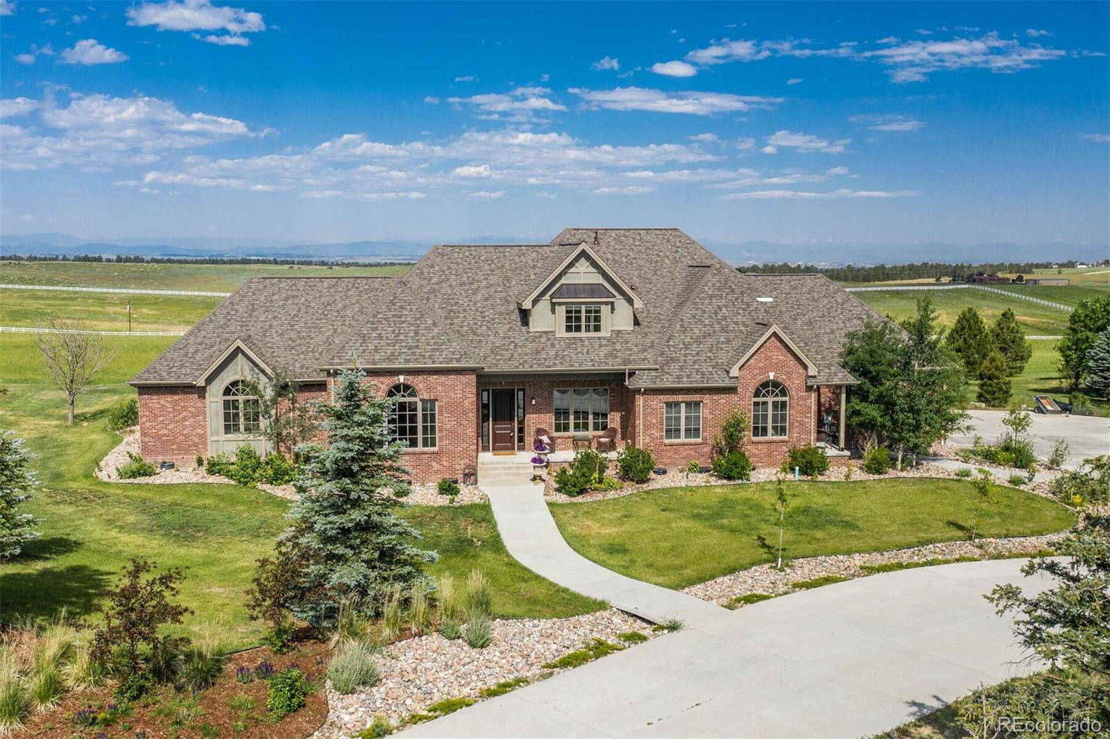 This custom estate sits high atop a hill on 38 acres and boasts spectacular, sweeping views of the entire Front Range. The interior is rich with custom finishes and quality craftsmanship. Gorgeous walnut hardwood floors, crown moldings, and upgraded tile work is found throughout the home using the finest materials.  The 2-story great room welcomes you where expansive windows perfectly frame breathtaking views.  The state of the art kitchen features a huge center islands with soapstone counters, custom knotty Cherry cabinetry, and professional grade, stainless appliances.  The open concept great room, kitchen and breakfast nook leads to the backyard!  The tranquility of the private main floor master retreat and spa like master bath is a nice escape!  There is a main level guest or nanny quarters with separate living space, bedroom, full bath and exterior entrance. Upstairs features a loft open to the great room and three large bedrooms with a full bath. The Guest House is within walkiing distance of the main home and boasts 3 additional bedrooms, plus custom kitchen, living room, 2 baths and another 3 car garage.  The Guest House is perfect for inlaws, a caretaker or possible rental property.  A rare find, the home is zoned for horses & outbuildings. The 1200 sq. ft, barn, shed and chicken coop make this the perfect property, all with a new hail resistant roof.  There is plenty of space to build horse facilities, a corral, or even a pool...the options are limitless!!!  Close in horse property with easy access to Parker, DTC, Park Meadows plus Douglas County Schools!  Views, views, views!