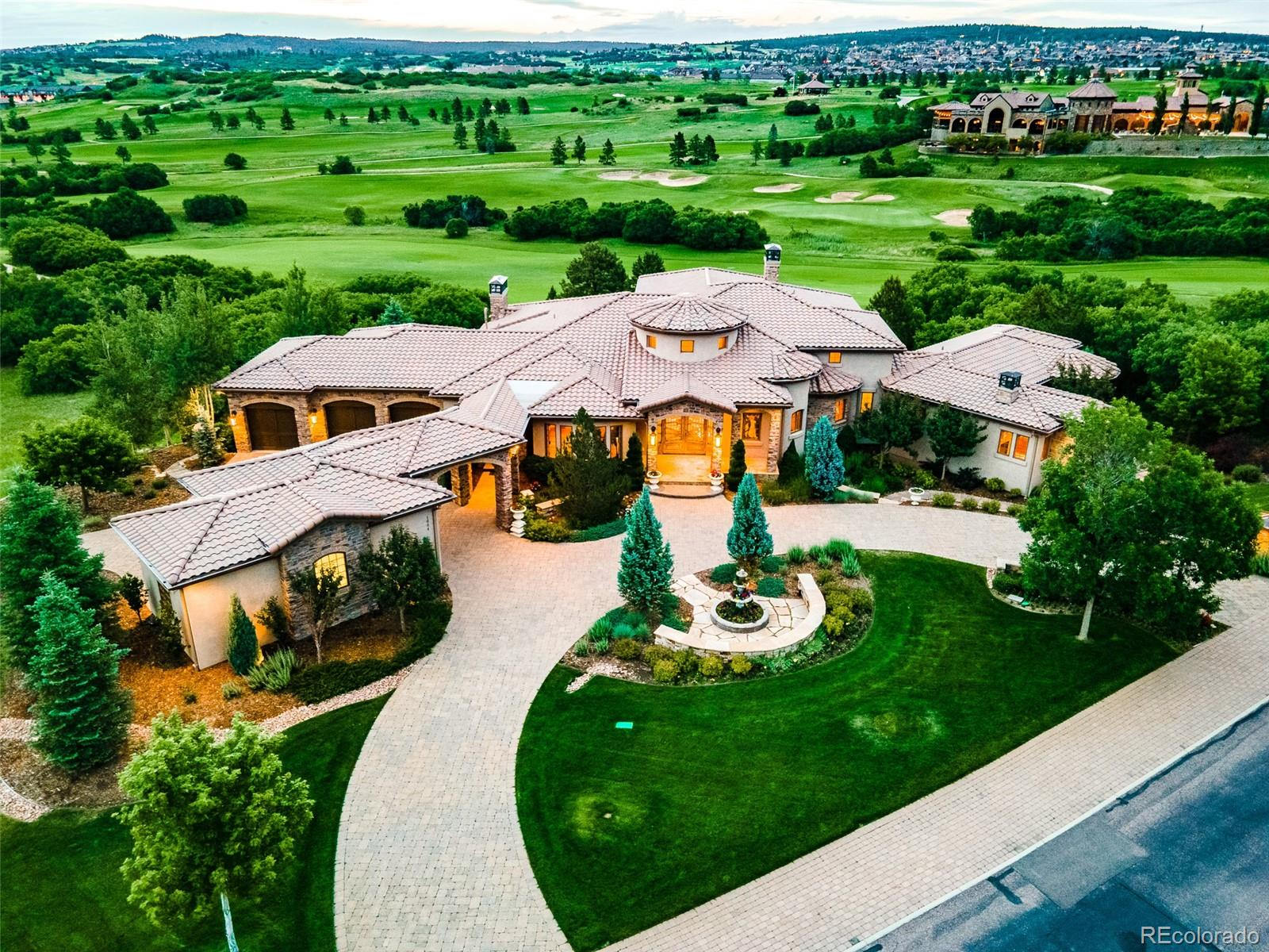 Layers of unparalleled decadence unfurl within this lavish estate nestled just minutes from I-25 in northern Colorado Springs. Over 1,200 sq ft of Tuscan-inspired outdoor living space crafts a resplendent composition that flows into a luxurious interior. Grounded by marble floors, an entryway steeped in grandeur sets the stage for an illustrious home to follow, including a nearby formal dining space with cascades of natural light. Revel in a great room defined by rich built-ins, a vast fireplace and floor-to-ceiling windows that overlook the golf course. A kitchen with top-tier appliances, miles of wood cabinetry and an island with seating beckons endless dinner parties with the convenience of outdoor access to the built-in kitchen and balcony. Each bedroom is en-suite, including a primary haven equipped with a peninsula fireplace, expansive walk-in closet and a private balcony. The bathroom is a masterclass in spa-like allure with a vast shower, deep soaking tub and serene lighting. A remarkable lower level sets new standards for at-home entertaining with a wet bar/mini kitchen, pool room, wine cellar, velvet-wrapped theater and multiple vignettes for private conversations. A secluded sauna suite amplifies the resort-like appeal of this home, functioning as a private spa for a heavenly retreat. This is Colorado Springs living at its finest.