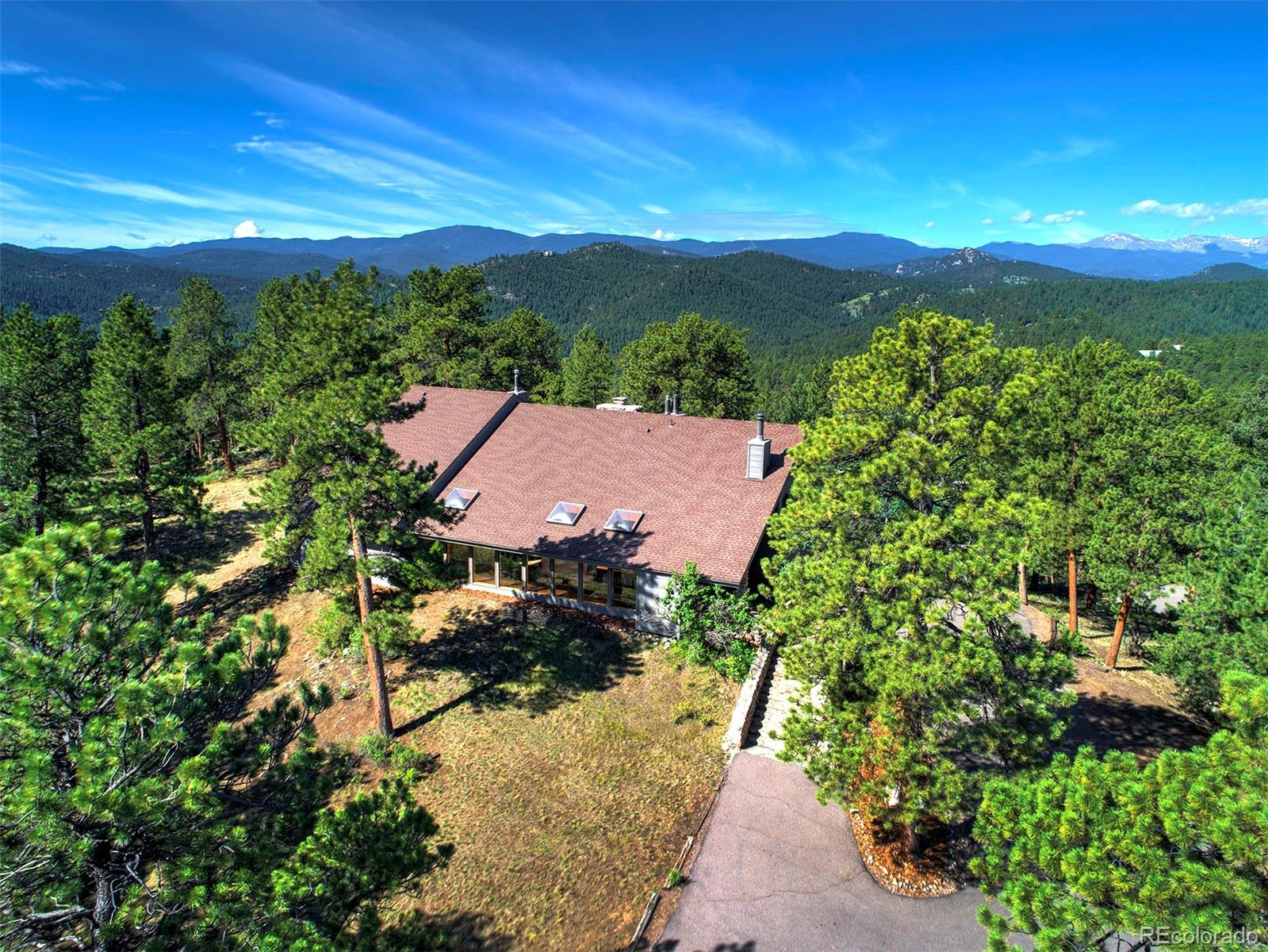 This classic mountain home is perched at the top of twelve gorgeous acres with spectacular Mt. Evans views. Property like this is hard to find anymore…conveniently located, easy access, serene, quiet and very private. This will be your lovely mountain retreat with quintessential mountain living in every room.  The center of the home is the expansive living room which boasts a floor-to-ceiling free-standing river rock fireplace flanked by towering windows and a 20' vaulted ceiling.  The remodeled kitchen features custom alder wood cabinetry with beveled glass, stunning granite counters, Subzero refrigerator, & beamed ceilings.  Enjoy your morning coffee and snuggle up with a good book on the numerous window seats around the house.  The mountain living experience is not limited to the inside of this wonderfully unique home, it will be easy to entertain on the expansive deck and enjoy watching the wildlife or the sunset over the snow-capped mountains. The hand-carved double doors off the living room lead you to the spacious master suite. Wake up to the fireplace flickering at your feet or step onto the deck. The large master bath is amazing with two walk-in closets, a jacuzzi tub, and a steam shower. Visitors will love sitting in the amazing library by the warmth of the antique wood stove. The home has a few more surprises with two staircases on each side of the house. One takes you to two charming bedrooms with a bathroom between. The other leads you to the perfect place to set up your home office or another bedroom with fireplace & en-suite bathroom. Closets & storage abound throughout. The Quartz Mountain neighborhood is a hidden gem, as is this home and property. It's rare to find this kind of secluded, quiet home & acreage so close to Evergreen with Mt. Evans views, easy access, paved roads & convenient location. Hiking & cycling just min away, 9 min. to Evergreen amenities, arts, music, festivals, fine dining & more.This is a true sanctuary & ideal CO lifestyle!