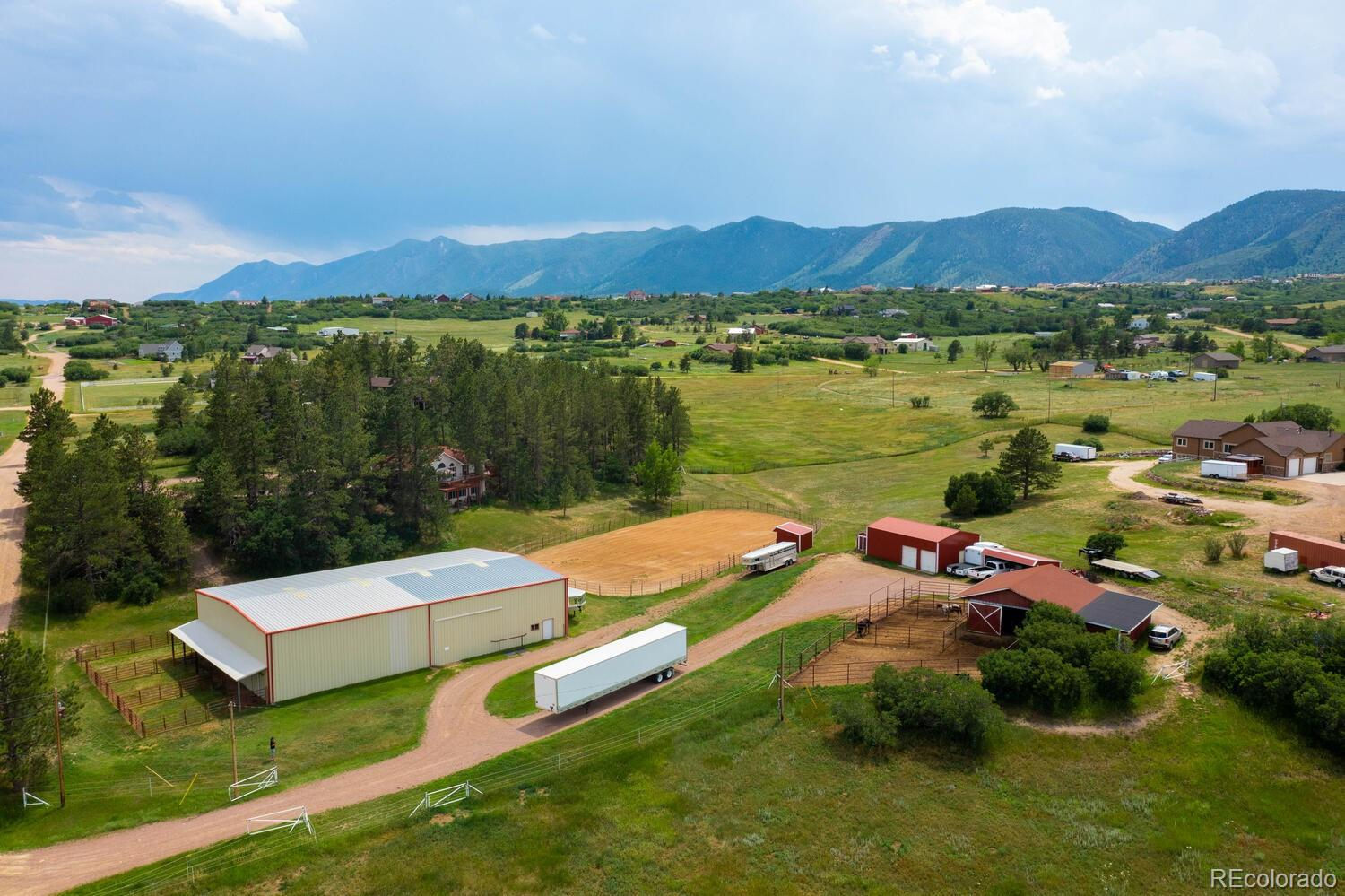 From rolling hills and complete equestrian amenities, this private five-acre retreat is nestled among beautiful pines. The shaded ranch-style home looks out to Pikes National Forest and showcases fabulous views of Mount Herman and the spanning foothills. Here is everything you'll need for equestrian living, including a 60x100' indoor arena, barn, outdoor arena, pastures, and loafing sheds. Plus, miles of riding trails connect you to Pikes National Forest adjacent to the property. With less than three miles to I-25 and downtown Monument, the location doesn't get any better!    When the day is done, kick off your boots and head to the comfortable home with a full walk-out basement. High vaulted ceilings, oak flooring and large widows furnish gorgeous views and fill rooms with loads of sunshine and natural light. An open kitchen ties in nicely with the main living space, and the delightful wrap-around deck surrounding three sides of the home is the ideal spot for relaxing and taking in the panorama of majestic mountains and grassy meadows.   Two gated driveways provide easy access to the property, which is fully fenced. The three-stall horse barn features padded floors, tack and hay room, automatic watering system and adjacent fenced-in pasture. An expansive indoor arena includes an additional five stalls with connected runs, and a separate vehicle/loafing shed is an added bonus. Park in the two-car attached garage while the oversized, detached two-car workshop is ideal for vehicles of all types. All buildings are in excellent condition and move-in ready. Here's your opportunity to live with your finest equines always in view.