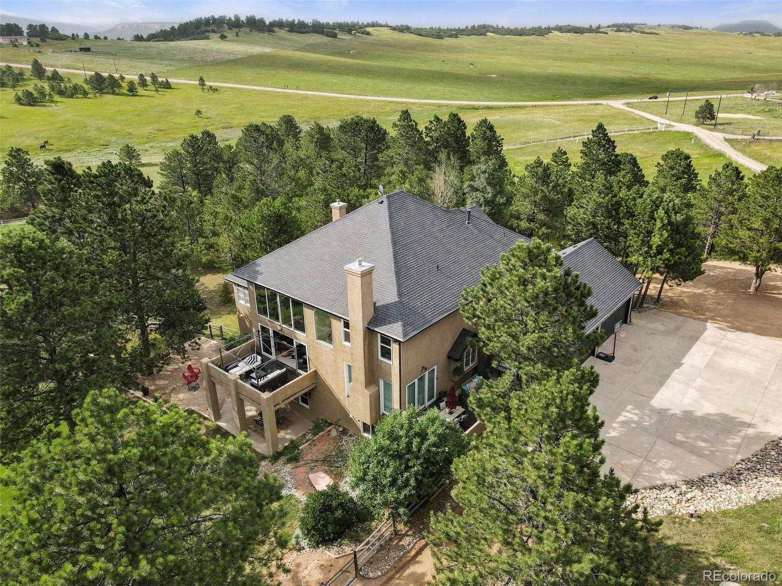 Stunning *sub-dividable* 21 acre custom horse property is the only modern estate of its kind with an unparalleled 2 minute drive to I25. Five minutes to Safeway and restaurants in a tranquil park-like setting with views from every oversized window! True Colorado luxury living combined with quick access to South Denver and Colorado Springs simply cannot be found anywhere else. Live on 21 gorgeous treed acres only 25 minutes to Park Meadows Shopping Center in Denver and 15 minutes to the Air Force Academy with Palmer Lake and Monument town centers each less than five minutes away and miles of trails a two minute trailer ride at Greenland Ranch- El Paso County taxes right on the Douglas County line! All 7400 sqft loaded with upgrades including real wood floors, oversized windows & plantation shutters, 21 ft ceilings in foyer with grand staircase and enormous great room with huge fireplace & access to large deck, 10 ft ceilings in basement with LVP, fireplace, wet bar & wine cellar w/ full guest bathroom and fifth and sixth beds framed in with doors and walk in closets (not dry walled - currently a gym & meditation room) and 7th jack & Jill bath roughed in & framed between, 10 ft ceilings in Master Bedroom w/ private deck, sitting area w/ fireplace and huge 5 piece bath and closet, 12 ft ceilings in the home office with fireplace, 9 ft ceilings in dream kitchen with 10 ft hard rock maple island, 2 ovens, 5 burner gas range, leather finish granite, remodeled mud/laundry room, 3 beds w/ en suite upstairs overlooking 2 story great room, 2x6 construction, 5 gas fireplaces, 2 gas stubs (no propane tanks!), 4 decks/patios for outdoor entertaining, 36x36 4-stall barn w/ tack room, two loafing sheds and paddocks, 70 x 160 ft arena with all 21 acres fenced for horses & over 1 acre fenced for dogs, no covenants, RV parking w/H2O & power! A rare find just 2 minutes to I25 w/ the new bridge at County Line - enjoy or subdivide into 5 acre lots for development in a prime location!