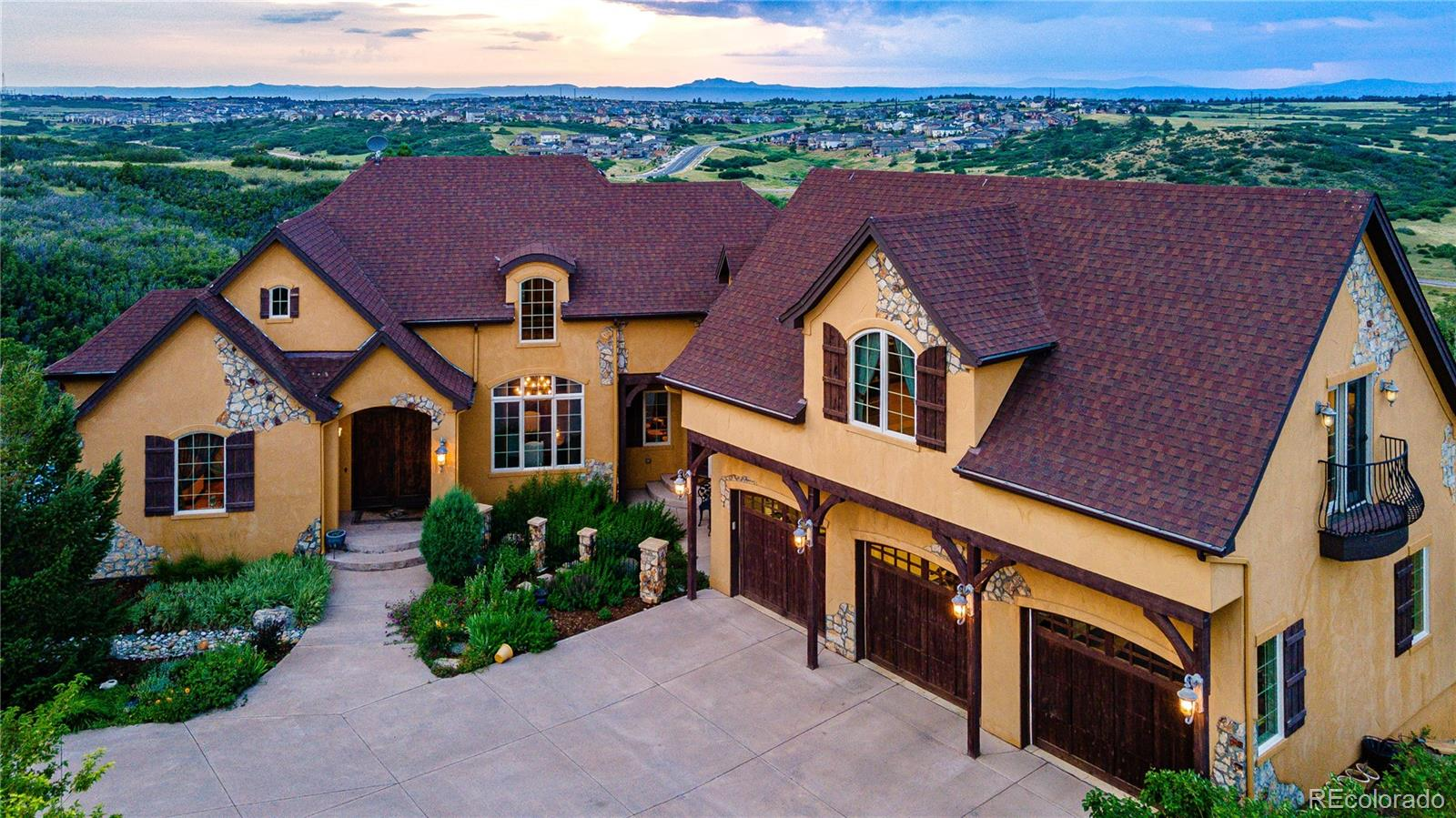 Imagine an Italian Tuscan Villa dressed in a Warm Ochre Stucco Exterior w Dramatically Exposed Rock Details, Juliet Balconies, Wood Beams & Rod Iron Accents Paired Perfectly w an Interior Reminiscent of a Rich Villa Combined w an Exquisite Custom Colorado Mountain Home Boasting Soaring Vaults, Walls Stone, Granite Slabs, Alabaster, Rod Iron, Copper, Travertine & 360 Degree Rocky Mountain & Open Space Views...Welcome Home! This well designed custom home features elegant interior appointments w an abundance of living & storage space in both the main residence & the carriage house. Five bedrooms & five baths reside in the main residence along w a gym, pub-styled bar, wine cellar, game room & office. The private master suite lives on the main level, boasting an oversized steam shower, jetted soaking tub, travertine tile, copper sinks, a bayed window retreat w magnificent views & a large walk-in w a custom cherry closet system. The upper-level mother-in-law living space includes a kitchenette, dining area, loft/flex space, bedroom, 3/4 bath & a private office. The lower-level features a magnificent pub-styled bar, wine cellar, game room, living room, gym, three bedrooms & two bathrooms. Outside an ideal carriage house boasts a wonderful living arrangement of one bedroom, one bath, kitchen, living & dining. Six oversized garage bays easily house all your vehicles & extra toys and include a charging station. The sparkling pool, pool deck, 3/4 bath & covered patio invite summertime fun & gated backyard playground paired w the trex deck and large patio accommodate all your outdoor entertaining needs with grace. This exclusive address lives on nearly four acres backing to dedicated open space which is perched perfectly on a cul-de-sac with surround views from Pikes Peak to Mount Evans and beyond. The proximity to central Castle Rock is ideal providing abundant dining, shopping, miscellaneous services, the Outlets, Tony's Market and quick commutes thanks to I-25 and Santa Fe.