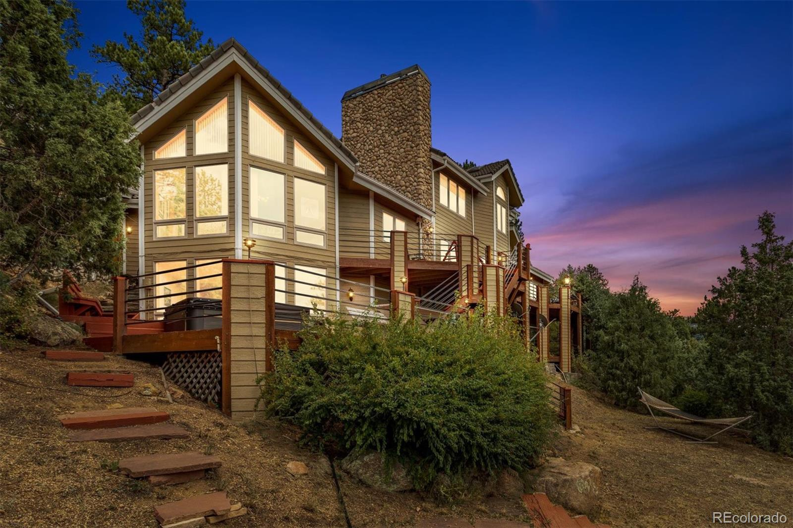 Large, custom home in north Evergreen, with sweeping Mountain Views! The end of cul-de-sac, 3.4 acre, private lot is mostly natural and pristine, and partly terraced for outdoor use and enjoyment. Large Windows bring that amazing view into almost every living space, while multiple decks invite you outside to play or just relax on the deck or in the hot tub, and breathe the clean mountain air. The deer and elks sightings are endless. Outdoors or indoors, this home entertains fantastically! Your family and guests will gather in the huge cherry wood kitchen and adjacent hearth room, or in the huge, vaulted living room with fireplace and a wall of windows to the West. They may also choose the walkout lower-level family room for TV and movies, or billiards, or whatever your preferred recreation. The Master Suite is on a floor by itself and enjoys its own fireplace and those coveted mountain views which extends even to the large, five-piece master bath. There are two office opportunities. One is on the level with the master suite, and the other is adjacent to the lower-level bedrooms. You will most certainly appreciate the attached four-car garage and the large workshop that was added on. Lots of guest parking and easy turn-around. And there's a treehouse! Plus much, much more!!