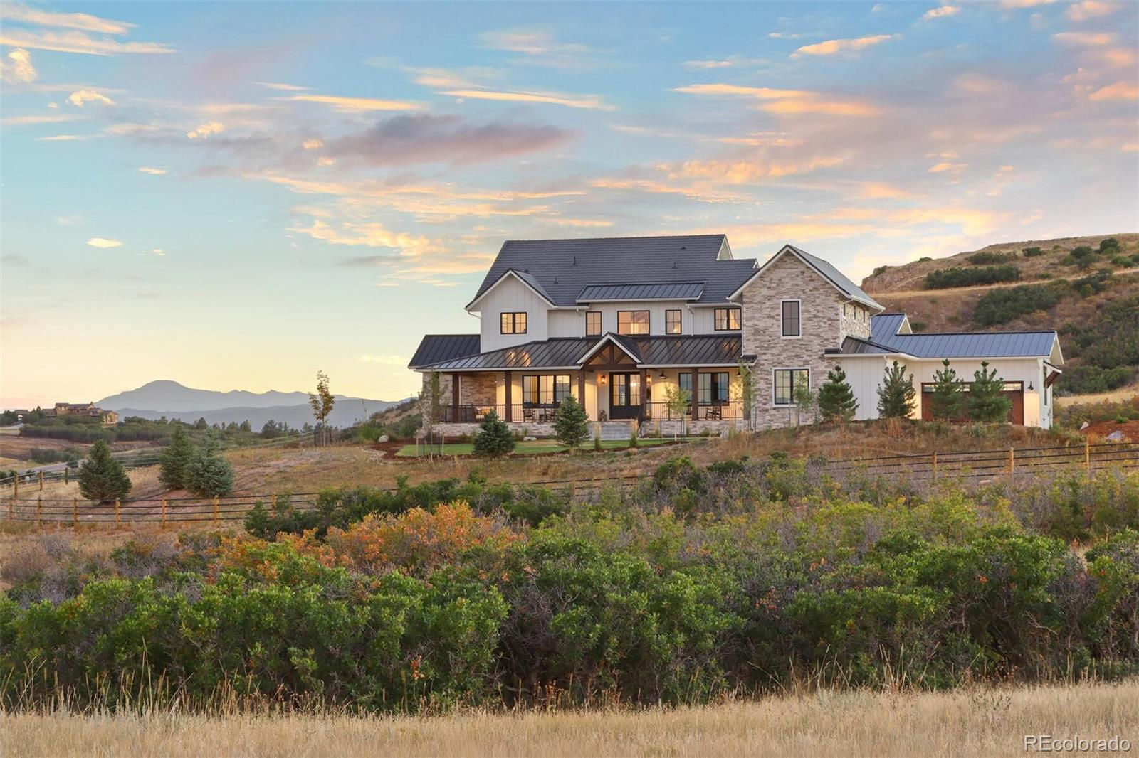 """An extraordinary sanctuary nestled within a breathtaking setting, this residence is truly an original, masterfully designed and constructed in 2020 with exquisite attention to detail. Artfully blending a style of modern farmhouse infused with European flair, this home offers views of Pikes Peak, Front Range and """"The Castle Rock."""" On 35 acres, the home and landscaping is enclosed by a post-and-rail fence and gated driveway. Inside, expansive windows provide sweeping views; outside, scenic living spaces include an inviting front porch, expansive rear deck, and a lower patio with fire pit and stone waterfall.   The foyer is magnificent, with French doors and 2-story ceiling dramatically appointed with an iron chandelier. The great room features a 24' vaulted ceiling with reclaimed wooden beams and a whitewashed brick fireplace. A striking wrought-iron staircase leads to the library loft, with a cantilevered landing for a unique suspended look. Start your day in the soul renewing sunroom, which is guaranteed to be a favorite room!  The gourmet kitchen and dining room is designed in a contemporary farmhouse style, with a wall of accordion-paneled doors that open to the deck. The walk-in butler's pantry is a room of its own, with butler's sink, microwave, beverage center, ice maker and storage galore!   The main-floor master is elegant and refined, with a walk-in closet, designed by California Closets®, and idyllic views of Pikes Peak. The master bath is astounding with fabulous views, white Carrara marble counters, and a freestanding tub.   The walk-out, lower level includes a rec room with a show-stopping wet bar and kitchen, plus a gym. There's a bunk room and a separate guest suite with an oversized, accessible ensuite.   The home includes state-of-the-art smart home automation and the land is zoned for two additional buildings if desired. Impressive and livable, this home offers a unique combination of style, setting, location, and privacy."""