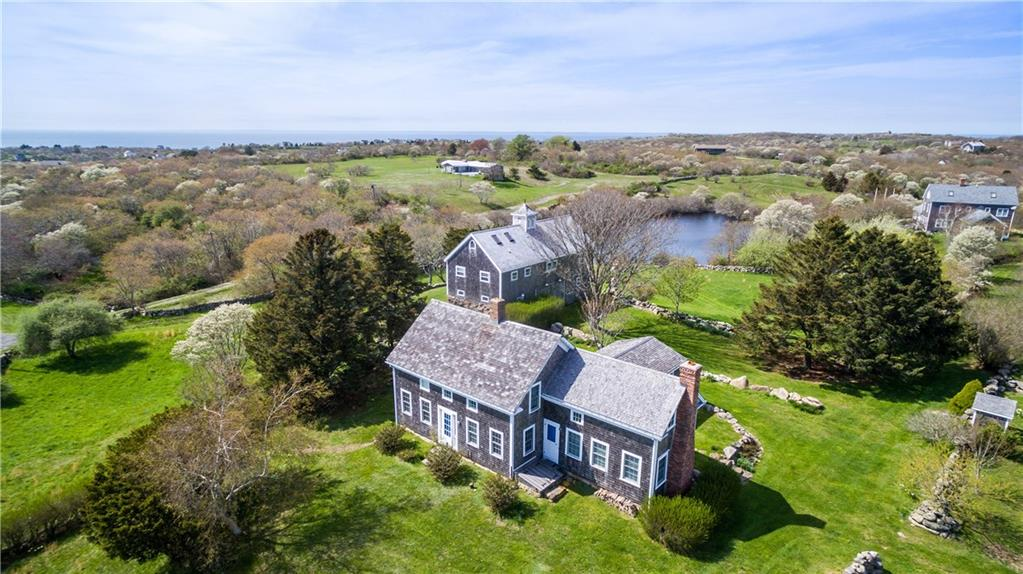 This exceptional property features a circa 1880's, stately Colonial home with an updated interior for the perfect Block Island retreat.  The spacious main floor includes a renovated classic living room with a wood burning, brick fireplace, an attractive kitchen with cathedral ceiling, Crown Point cabinetry, soapstone countertops and French doors leading to a sunny patio, entry hall with powder room, a private dining room and a light-filled master bedroom with marble full bath.  The unique second level harkens back to when the property was a working farm and housed orphans to work the farm living on the second floor of the house.  Three bedrooms, one full and one half bath complete this space.Behind the house is the fully renovated, original 1880's barn with living quarters on the second floor.  The gorgeous family gathering room has a Post & Beam design for summer parties and getaways.  Second floor also has one bedroom, full bath and loft area accessed by an architecturally interesting spiral stairway.This magical setting has southerly views overlooking beautiful Rodman's Hollow to the Atlantic Ocean, fields with stonewalls running through out and a picturesque pond to the west that the family has enjoyed for swimming, canoeing and fishing.  Abutting conservation land to the east, this is the quintessential Block Island property to cherish for years to come.