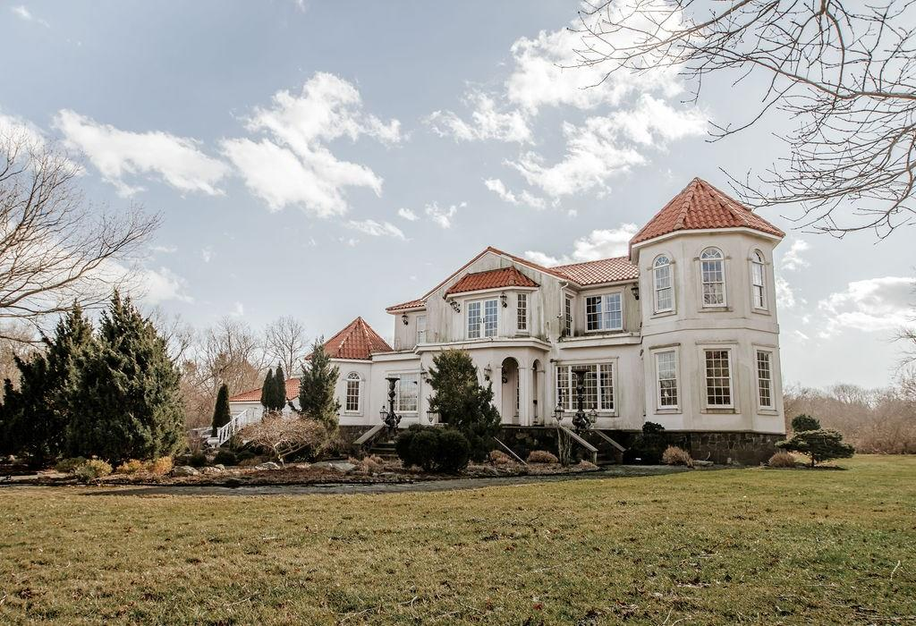 Exquisite craftsmanship and extraordinary details seamlessly combine to create a fabulous 4,759 sq ft Mediterranean style estate on five acres with views of the glistening waters of Narragansett Bay. An ornate entrance with a stunning staircase is flanked by elegant living and dining rooms along with gleaming hardwood floors making this home feel truly grand. A spacious gourmet kitchen w/ stainless steel appliances and refrigerated wine storage sits alongside a restaurant-quality wet bar made for entertaining. An adjacent family room with a custom painted dome ceiling and stone fireplace overlooks the majestic grounds complete with courtyard gardens, a magnificent fountain, statues and extensive back patio. Two gracefully appointed master suites have ample closet space and spectacular views of the sweeping lawns, gardens and landscaping. Upper level offers three additional bedrooms, three full bathrooms, a home office with built in cabinetry, and French doors that open up to ocean views. Four additional fireplaces, multiple hand-painted murals by local artists, and custom antique fittings throughout make this home especially unique. Situated in the famed Ocean Drive Historic District neighborhood, you'll be a stone's throw from the beach, golf, dining, parks and recreation.