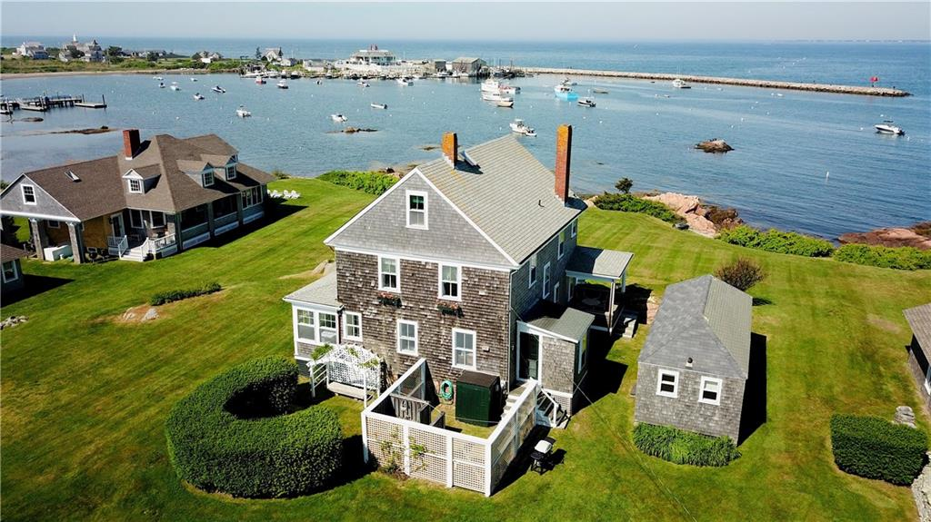 """Historic Family Compound Overlooking Sakonnet Harbor  Located on 1 plus acres at 10 and 9 Minnesota Road, the Compound consists of The Big House, built in 1900, an adjacent bungalow, the nearby White House built in 1935 and a mooring.  The Big House, #10, a classic 3 floor summer home built on a ledge above the flood zone, and further protected by the Sakonnet Harbor Breakwater, has survived all the hurricanes that nature could throw at it, including the catastrophic one in 1938. A porch which overlooks a large lawn, the mooring and rocks where people swim, provide a commanding place for gatherings and viewing the Harbor with all of its activities and spectacular sunsets. The first floor living room, with a fireplace, and a sunroom also over- look to the harbor. A kitchen, dining room, butler's pantry and a half bath round out the first floor. 4 tastefully decorated bedrooms with two full baths are on the second floor and there is a bedroom, bath and storage on the third floor. A 2 bedroom 1 bath bungalow, affectionately called the Guest House is nestled on the north side of the house. Across the expansive lawn to the east is #9, The White House, an adorable 3 bedroom 2 bath summer cottage, the front of which is covered with climbing roses. The large garage is ideal for storing a car, bikes, or a boat over the winter.  This historic place says """"Sakonnet"""" like no other. It is time for another family to make its memories.  Buyer  to pay the LCAT at the recording of the deed."""