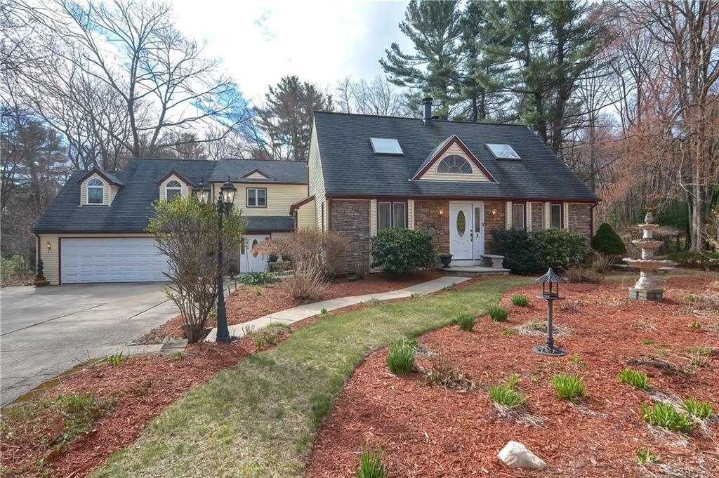 This 4-5 bedroom expanded cape is the perfect home for a large family, or multigenerational living.  The main portion of the home features an open floor plan, complete with cathedral ceilings and fireplace in the sun drenched living room, a first floor bedroom with and adjoining full bathroom that is handicap accessible, and an open concept kitchen and dining area. Off the dining space you will find a slider that leads out to an oversized, multi level deck. You will also find an additional full bathroom and two well appointed bedrooms (one with a balcony) on the second floor.  The in-law features 1-2 bedrooms, an open concept living space, a full bathroom, as well as a formal sitting room, a family room with egress out to a balcony with beautiful views of the impeccably maintained grounds, a large kitchen with an island and dining space.  This home also has a plethora of storage space throughout.  Additional features include, irrigation, central air, beautifully landscaped grounds, chair lift, convenient location to local amenities and highways, a 2 car attached garage with access from both the main home and the in-law, and so much more!