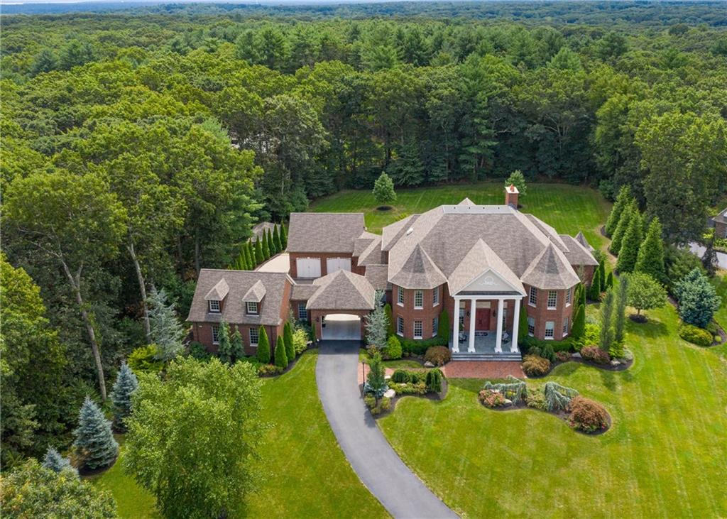 Enjoy elegant, easy living in this custom brick manor-style home. Top quality finishes and fine craftsmanship are evident throughout, with highlights such as a sweeping, custom double staircase, Brazilian cherry floors with black walnut inlay, 20' ceilings, mosaic tile details, Schonbek lighting, Veissman mechanicals. A first floor owner's suite features a sitting area, gas fireplace, soaking tub, separate vanities, a double shower and exterior patio access. A stunning foyer with 20' ceilings opens to the family room with fireplace and exterior access to the patio. The kitchen leaves little to be desired, with a Wolf cooktop, double ovens, warming drawer and Subzero refrigerator, custom cabinetry, stone sink, and an expansive island with double thick granite. Additionally, a butler's pantry and laundry room are found off of the kitchen. A dining room with fireplace, office showcasing french doors and oversized windows, and a half bath complete the first floor. The newly finished second floor includes three ensuite bedrooms with baths finished in granite and tile. There is also a lofted den/office on the second level. An unfinished basement provides potential for expansion and has radiant heated floors. Four car garage, one with loft space for storage, and a paver courtyard allow for plenty of parking. Both the front and back of the home offer bluestone patios, and the grounds offer mature plantings and landscape lighting. A unique opportunity to own a truly turnkey home.