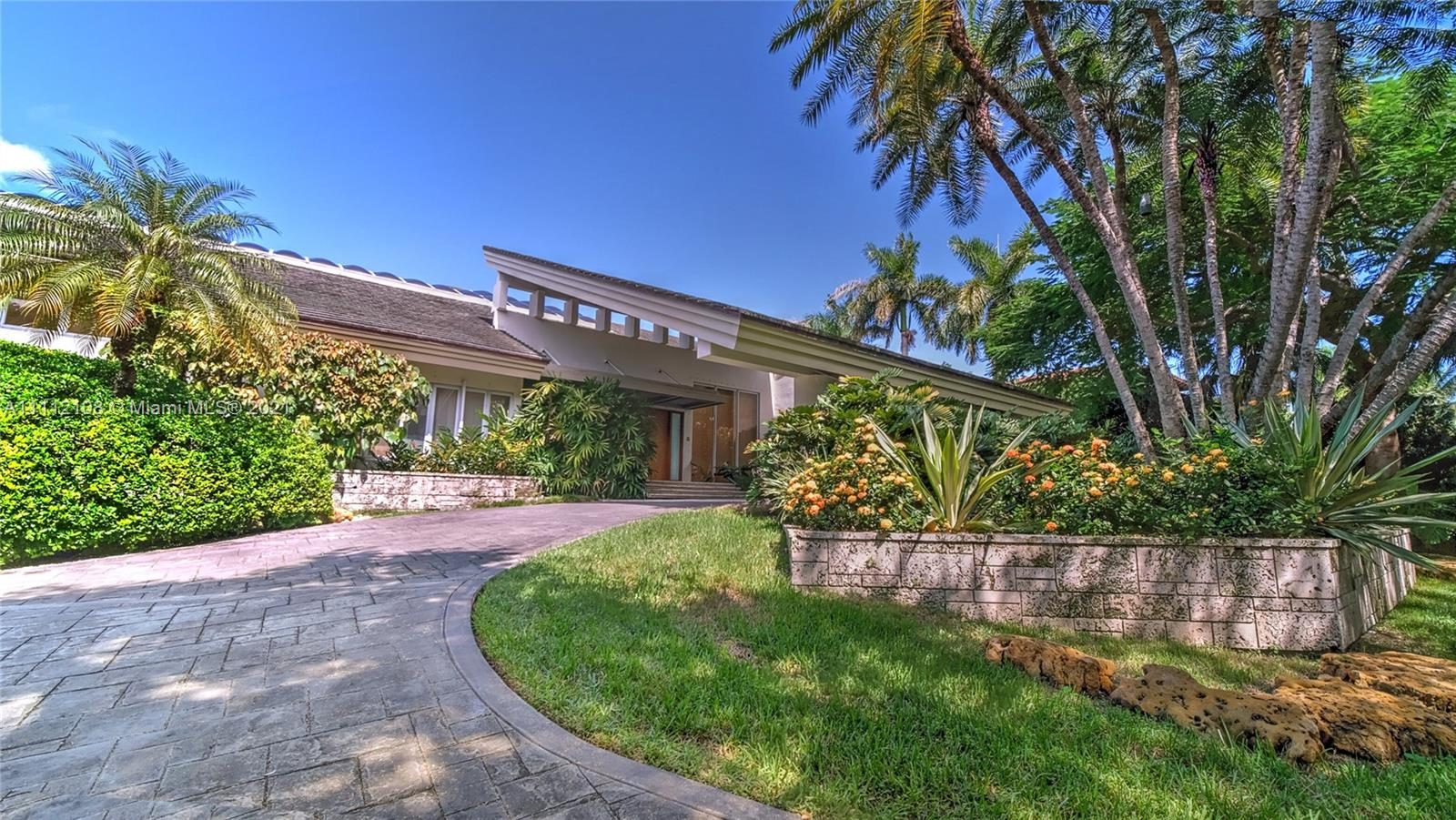 Fabulous Miami Modern waterfront home in glamorous, gated Gables Estates boasts grandly scaled dbl-height interiors and cascading natural light. Level 1 includes oversized living, dining, family w/fireplace, wet bar & pool views, library/office, home theater, eat-in kitchen appointed w/Sub-Zero, Wolf & Miele + pantry & breakfast rm; 3-bdrm suite for staff or teens; plus cabana bath, laundry & attached garage. Level 2: Enormous primary suite w/sumptuous bath & huge walk-ins; 4 unique en suite bdrms designed w/private lofts. Light hardwood flows thruout. Huge gym +bonus space. Wonderful covered outdoor living area & BBQ frames huge tiered patio & pool laid in native oolitic limestone. 16-ft elevation; lush tropical landscape, 180 waterfront ft, 66-ft dock, minutes to open bay. Paradise!